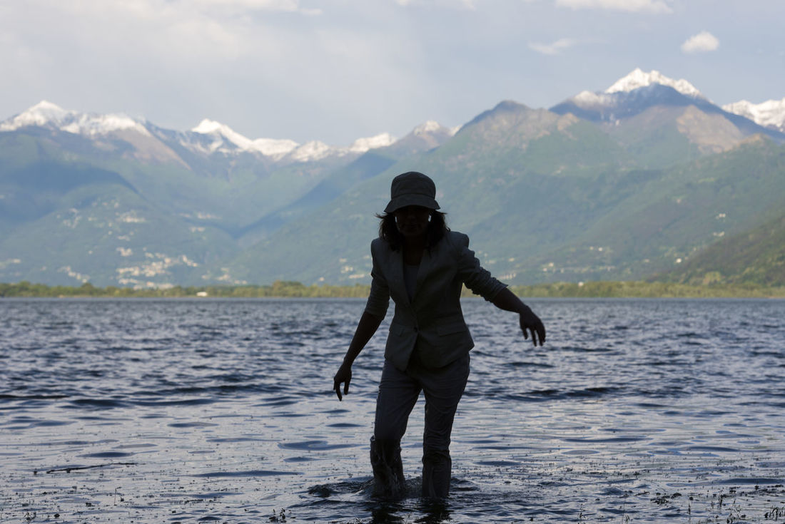 Woman walking in the water in an alpine lake Maggiore with snow-capped mountain in Ticino, Switzerland. Adult Adventure Alpine Lake Beauty In Nature Casual Clothing Day Hat Idyllic In The Water Lago Maggiore Lake Mountain Mountain Range Nature One Person Outdoors Scenics Silhouette Snow-capped Swiss Alps Tranquility Walking Water Wet Woman