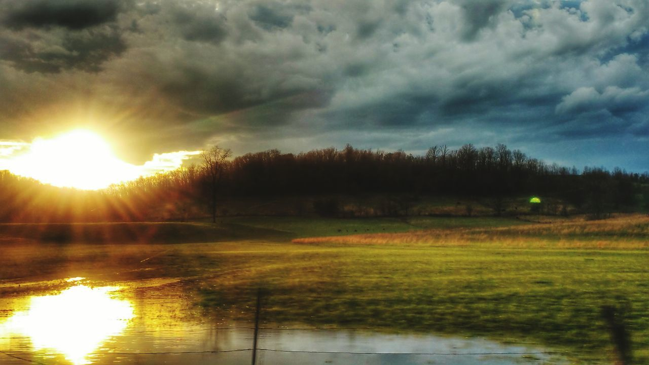 nature, scenics, tranquility, beauty in nature, sky, tranquil scene, sunset, cloud - sky, reflection, sunbeam, sun, idyllic, no people, outdoors, lake, sunlight, landscape, tree, water, grass, scenery, day