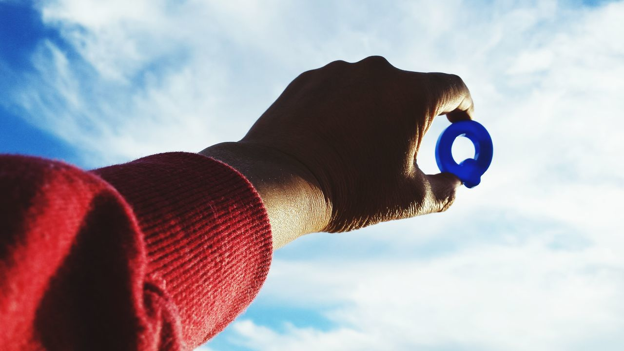 Cropped Image Of Hand Holding Letter Q Against Sky