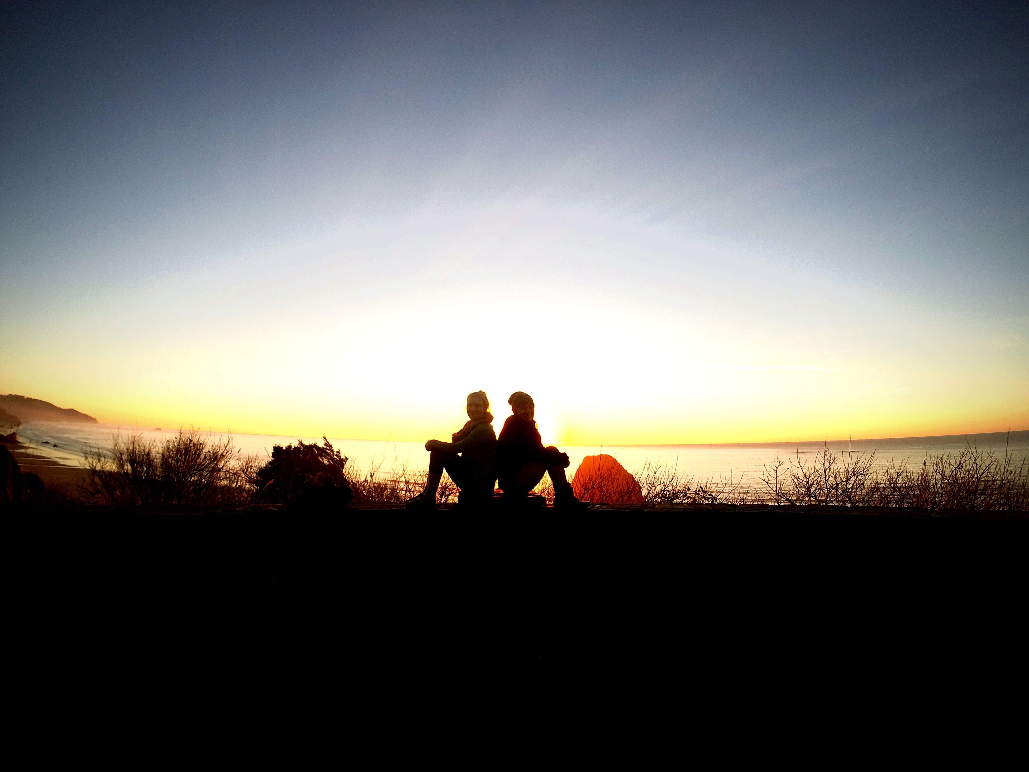 sunset, silhouette, sea, water, horizon over water, copy space, lifestyles, orange color, leisure activity, scenics, togetherness, beauty in nature, men, tranquil scene, tranquility, sky, clear sky, sitting