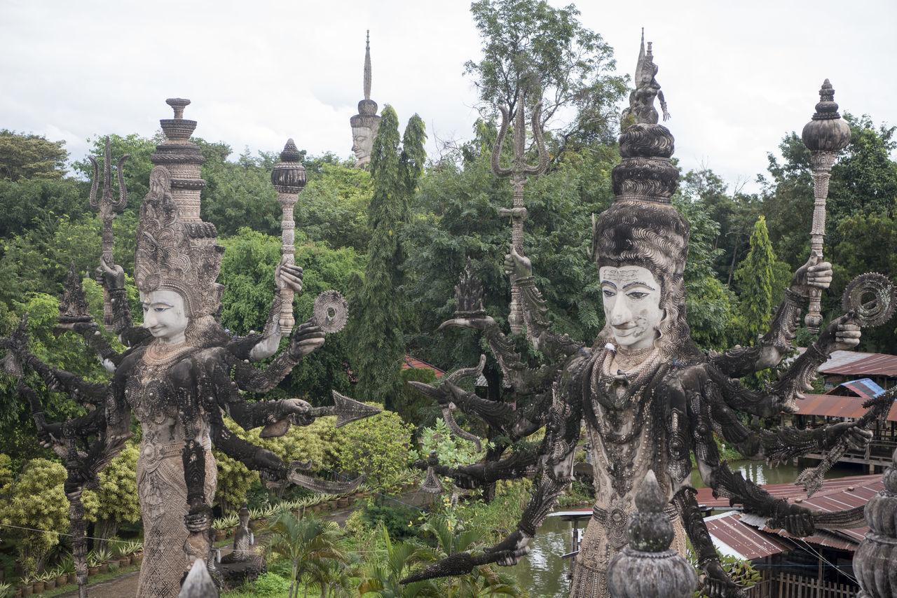 Ancient Statues Amidst Plants Against Sky