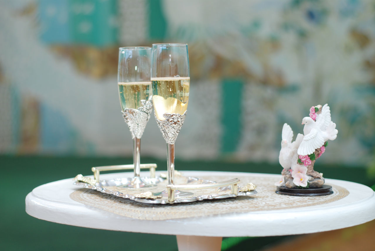 Two glasses gap-filling champagne and little porcelain figurine of white pigeons stand on a table Alcogol Beauty In Nature Close-up Day Drink Drinking Glass Focus On Foreground Indoors  No People Shampagne Table Wineglass