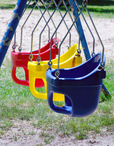 colorful baby swings wait for young kids to play in them and soar into the sky Fun Red Swing Set  Baby Swings Blue Day Empty Grass Nature No People Outdoors Outdoors Photograpghy  Park Playground Safety Sunlight Yellow