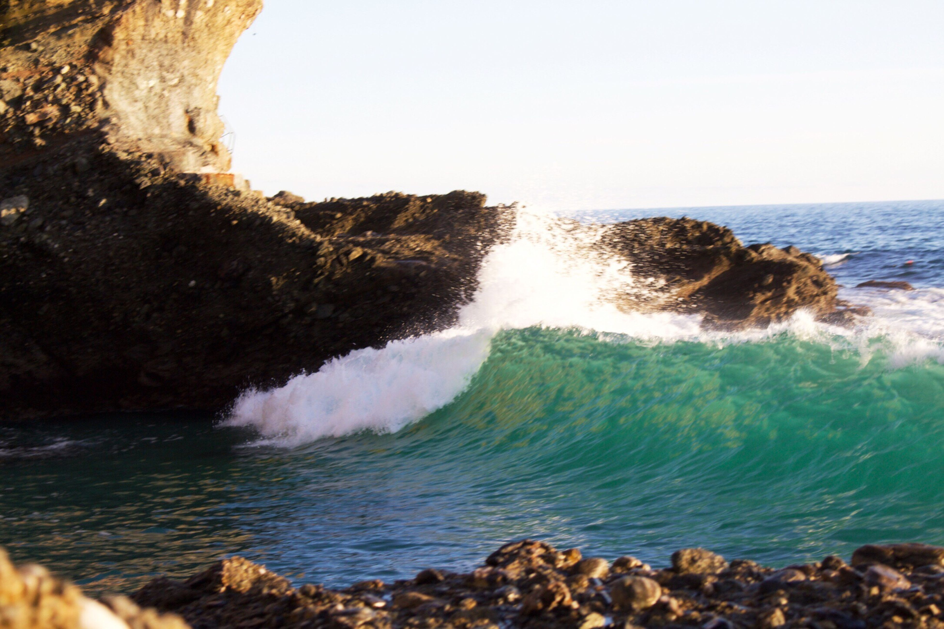 water, sea, rock - object, beauty in nature, scenics, clear sky, nature, motion, rock formation, horizon over water, tranquil scene, surf, wave, tranquility, splashing, rock, idyllic, blue, day, outdoors