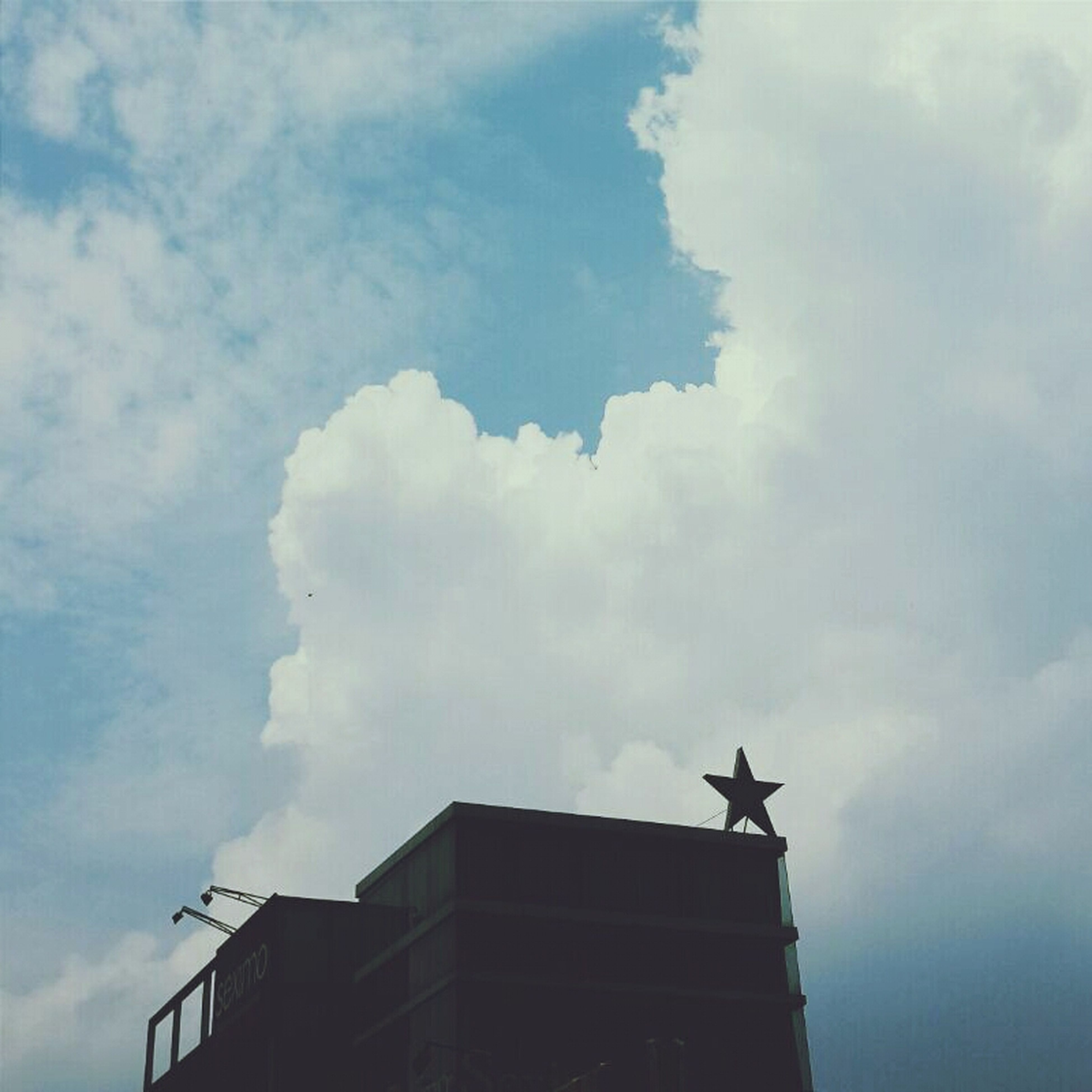 low angle view, sky, cloud - sky, building exterior, architecture, built structure, cloudy, cloud, bird, animal themes, outdoors, animals in the wild, day, wildlife, human representation, high section, building, one animal, statue, no people