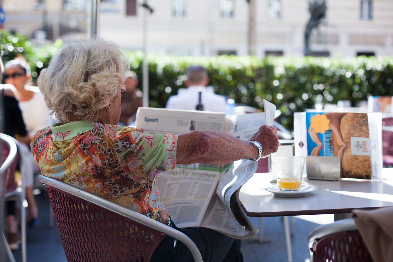 real people, incidental people, built structure, building exterior, senior women, women, focus on foreground, senior adult, outdoors, day, sidewalk cafe, architecture, leisure activity, city, lifestyles, newspaper, food, close-up, freshness, human hand, people