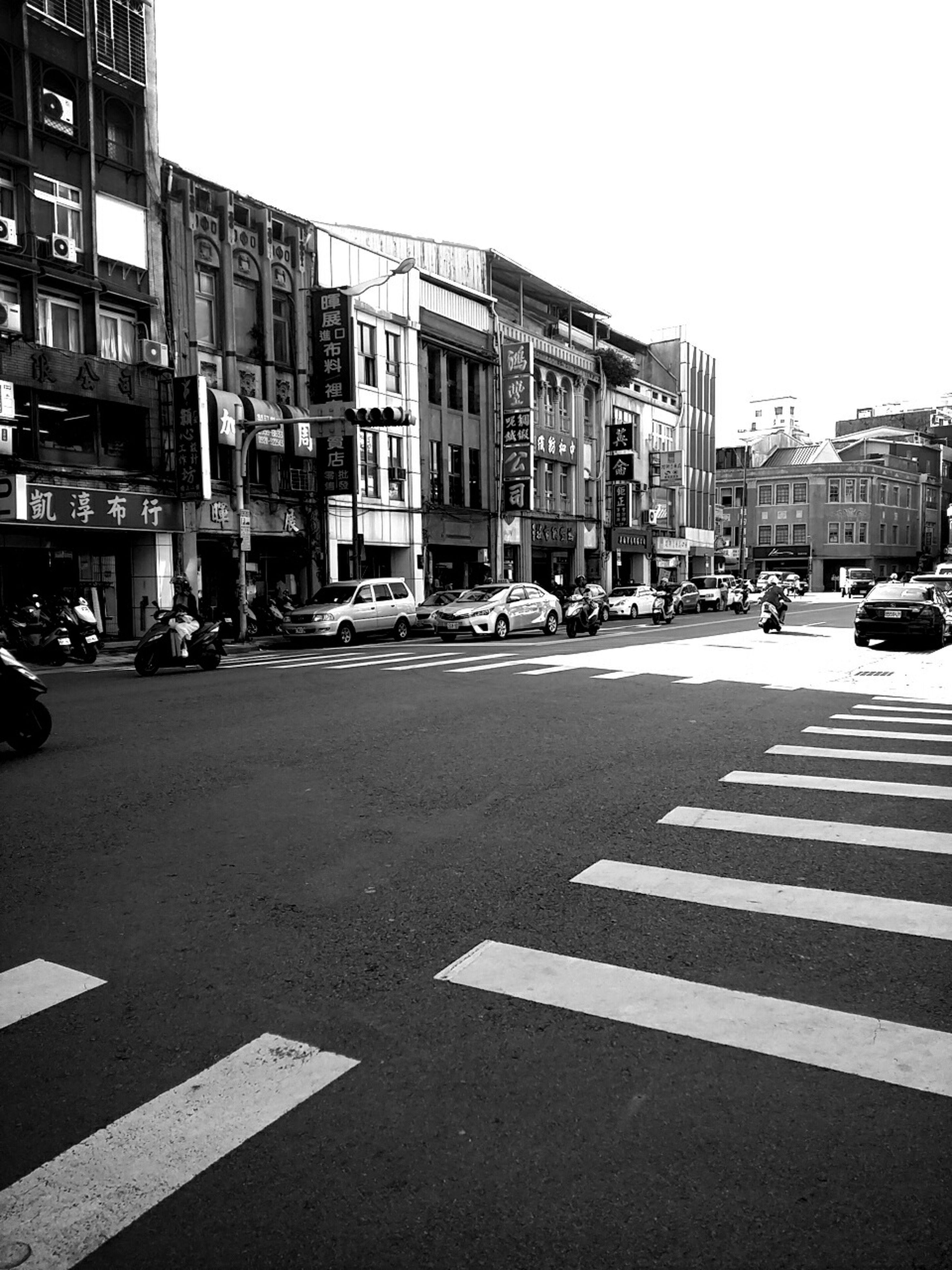 building exterior, road marking, street, architecture, city, built structure, transportation, road, car, city street, zebra crossing, city life, land vehicle, road sign, incidental people, arrow symbol, asphalt, mode of transport, the way forward, guidance