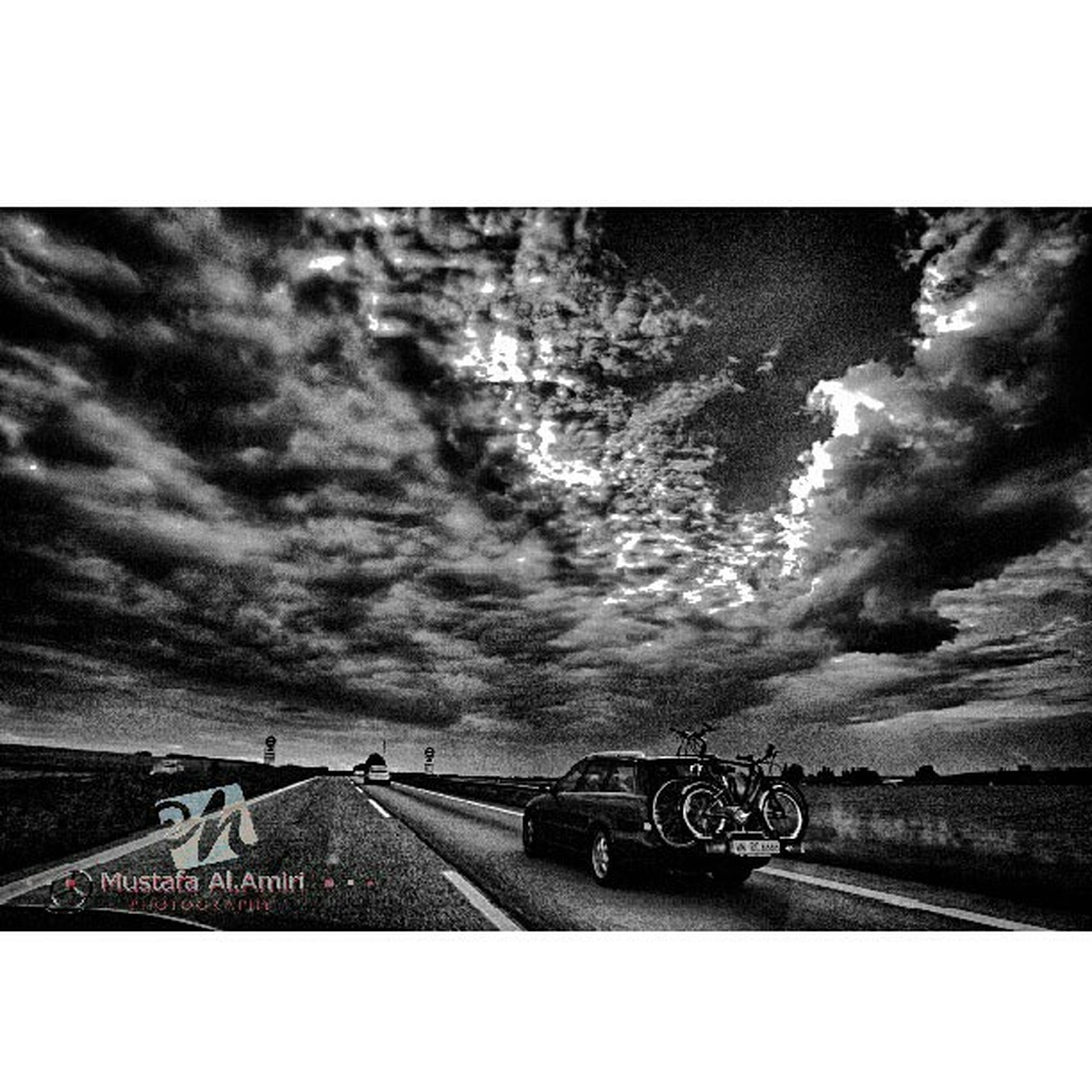 transfer print, transportation, sky, auto post production filter, road, cloud - sky, mode of transport, land vehicle, the way forward, road marking, cloudy, car, cloud, mountain, street, outdoors, diminishing perspective, overcast, no people, day