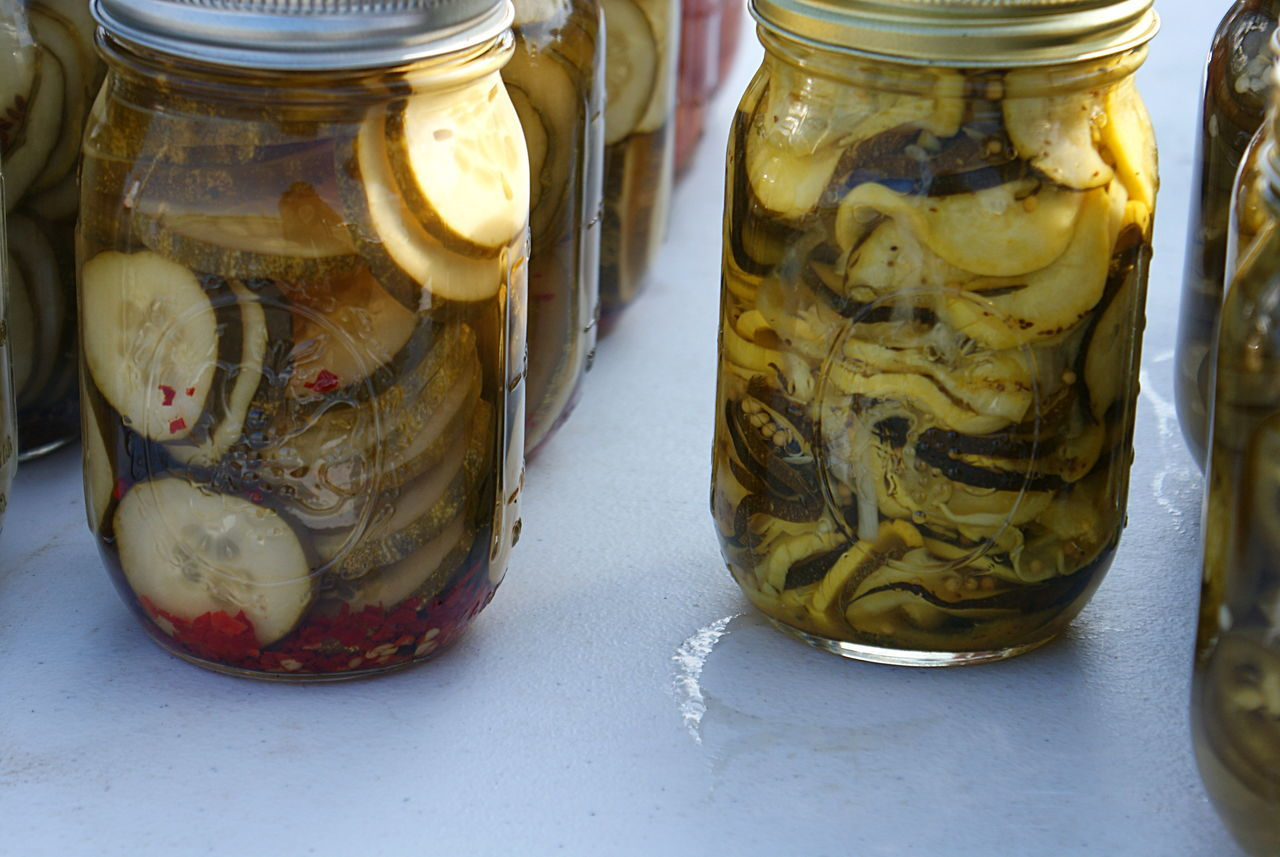 Colorful food in jars: cucumber pickles and yellow squash and zucchini pickles, in the sunlight. Bread And Butter Pickles Close-up Cucumber Day Food Green Color Homemade Food Jar Jars  No People Pickles Preserved Squash - Vegetable Sunlight Vegetables Yellow Color Zucchini