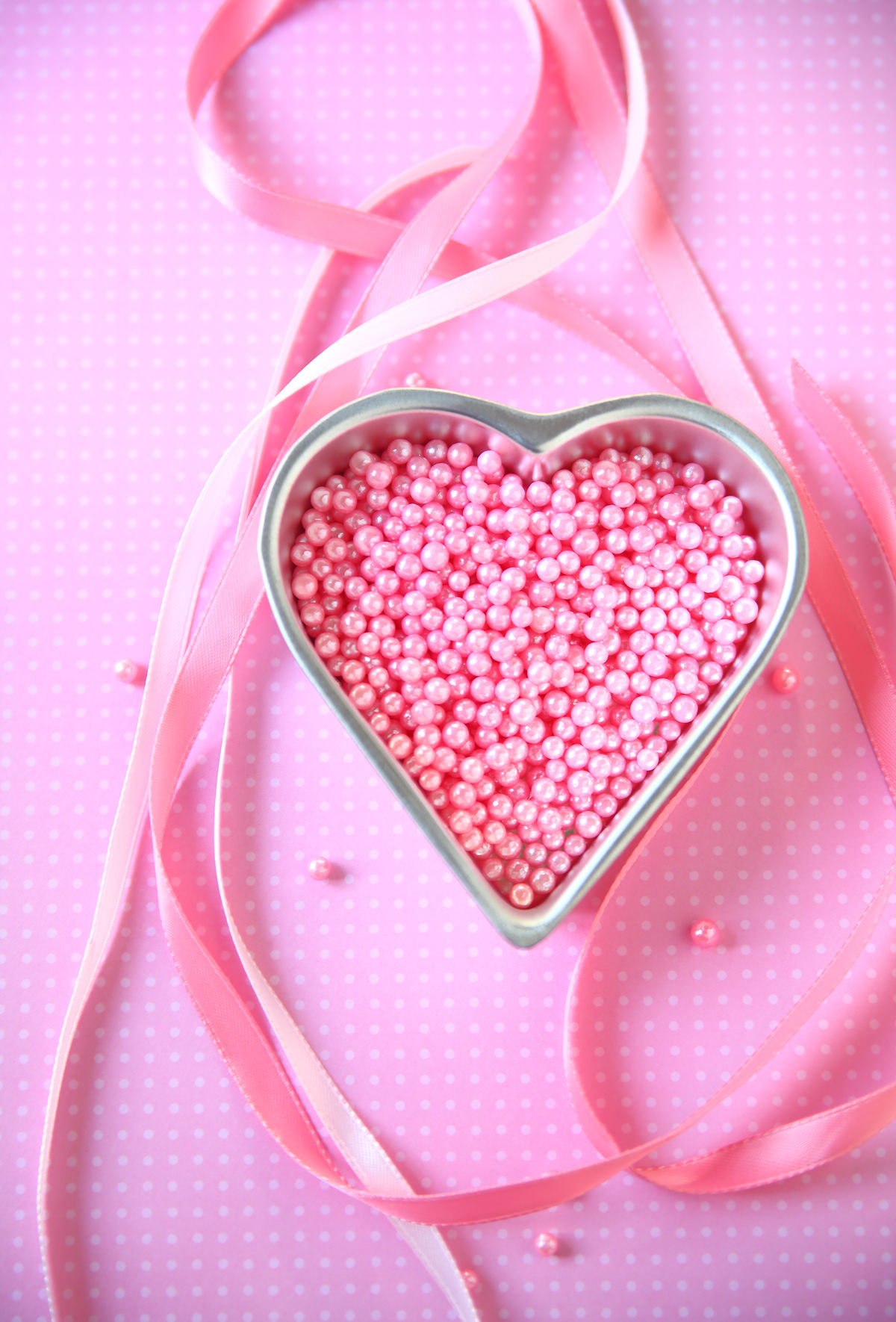 Pink beads in heart pan on polka dots Candy Close-up Colored Background Day Decorative Feminine  Girly Heart Shape Indoors  Love Natural Light No People One Color Overhead Pastel Colored Pattern Pink Background Pink Color Pink Ribbons Polka Dot Studio Shot Sweet Food Valentine's Day - Holiday Vertical