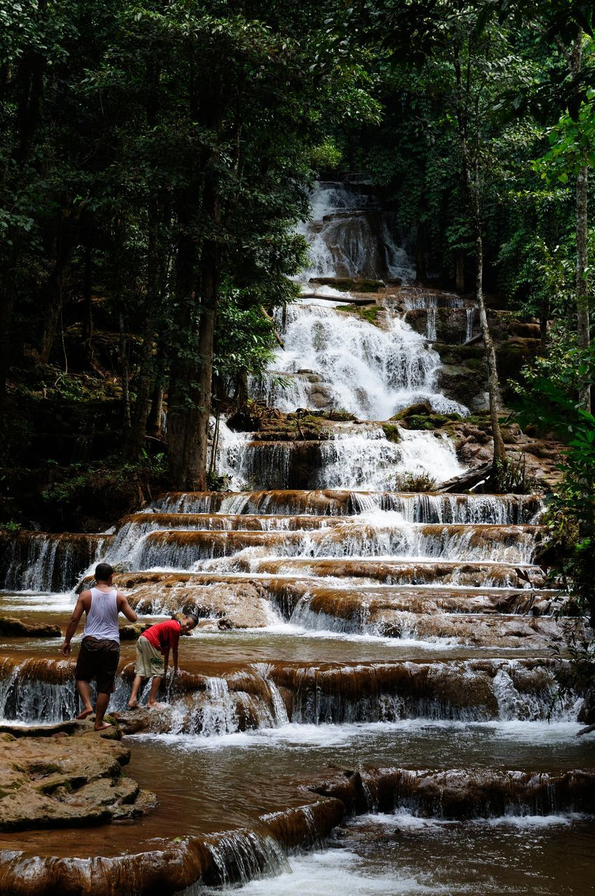 waterfall, real people, water, nature, rock - object, tree, forest, motion, day, beauty in nature, leisure activity, men, outdoors, togetherness, lifestyles, women, standing, scenics, vacations, young adult, mammal, people