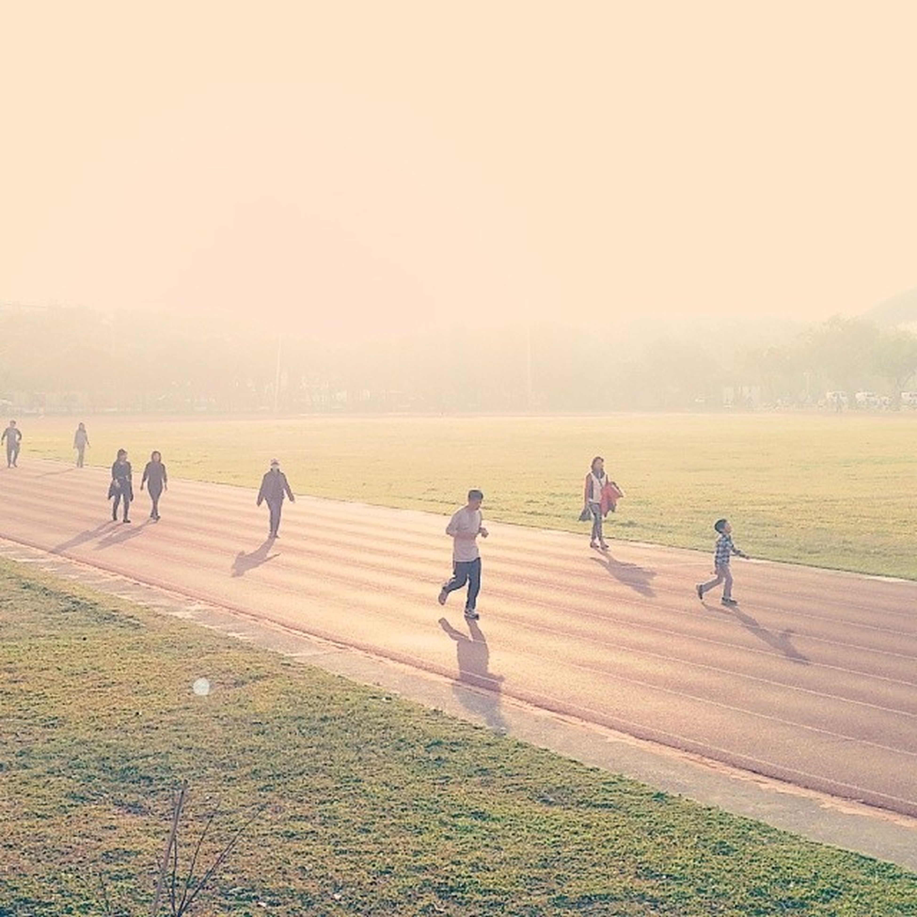 men, lifestyles, leisure activity, field, copy space, full length, walking, clear sky, grass, landscape, person, bicycle, nature, large group of people, togetherness, sky, running, medium group of people, outdoors