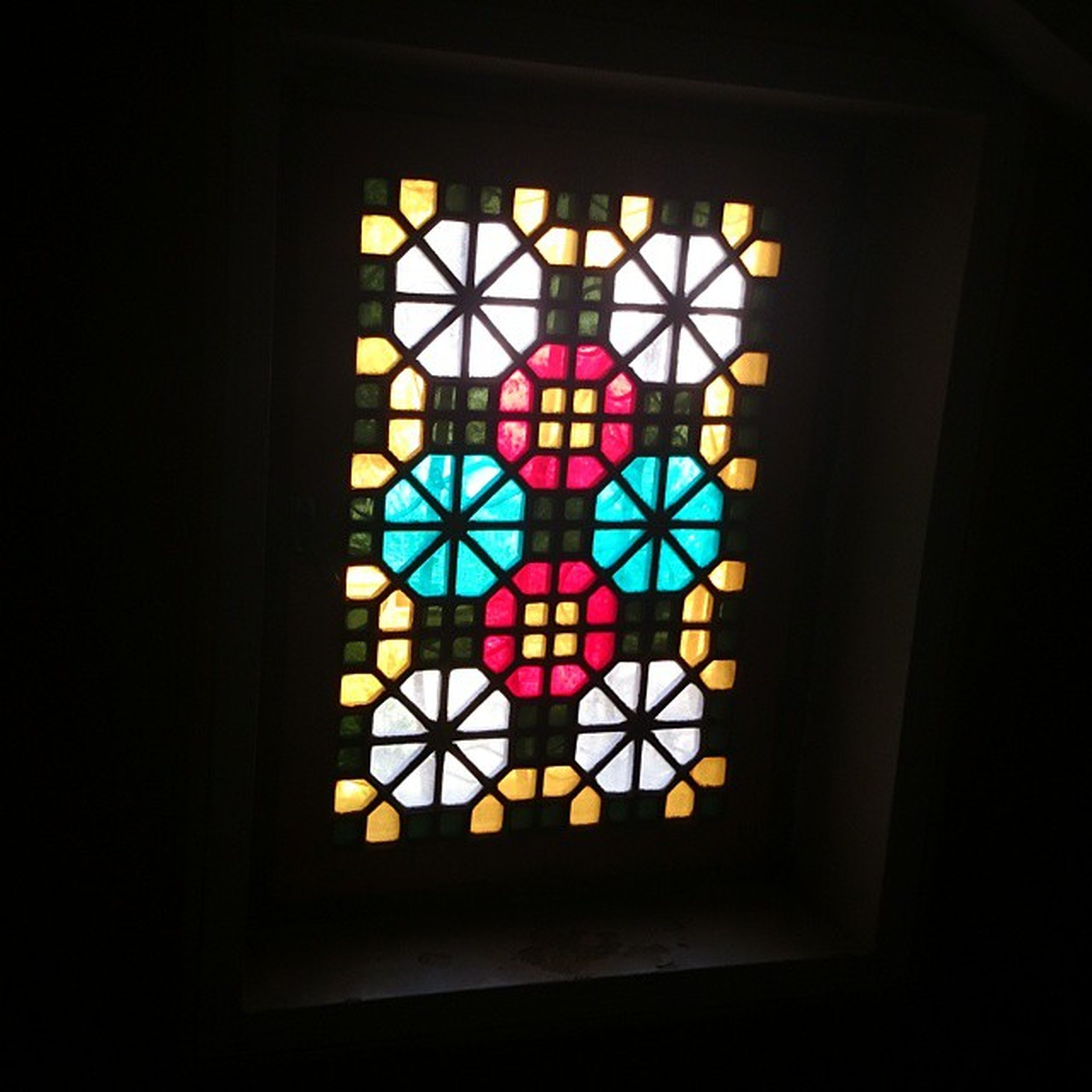 indoors, window, illuminated, glass - material, stained glass, multi colored, low angle view, pattern, decoration, built structure, transparent, glowing, architecture, design, lighting equipment, geometric shape, no people, home interior, dark, religion