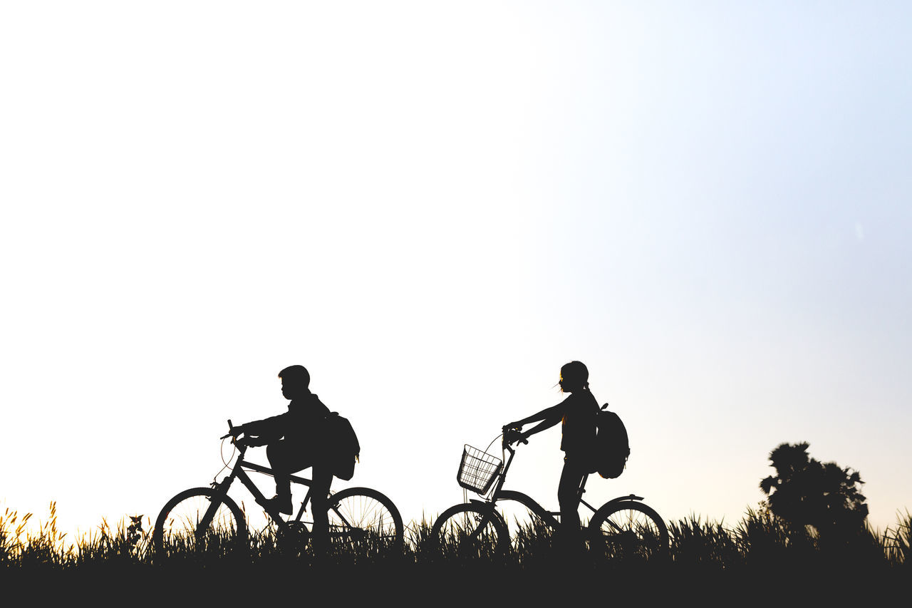 bicycle, silhouette, clear sky, cycling, transportation, real people, men, leisure activity, copy space, field, riding, lifestyles, land vehicle, mode of transport, outdoors, sky, nature, day, two people, grass, togetherness, boys, landscape, tree, scenics, full length, mountain bike, bonding, cycling helmet, headwear, people