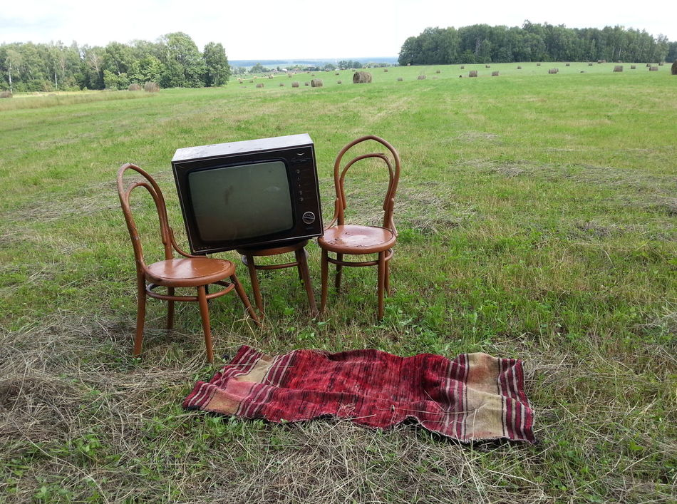 A weird installation on a field in Russia Chairs Day Field Field Furniture Grass Green Color Illegal Dumping Installation Junk Living Outside Living Rough Nature No People Old Days Old Television Outdoors Past Times  Pointless Ridiculous Rubbish Russia Television Set Unwanted Weird Lieblingsteil