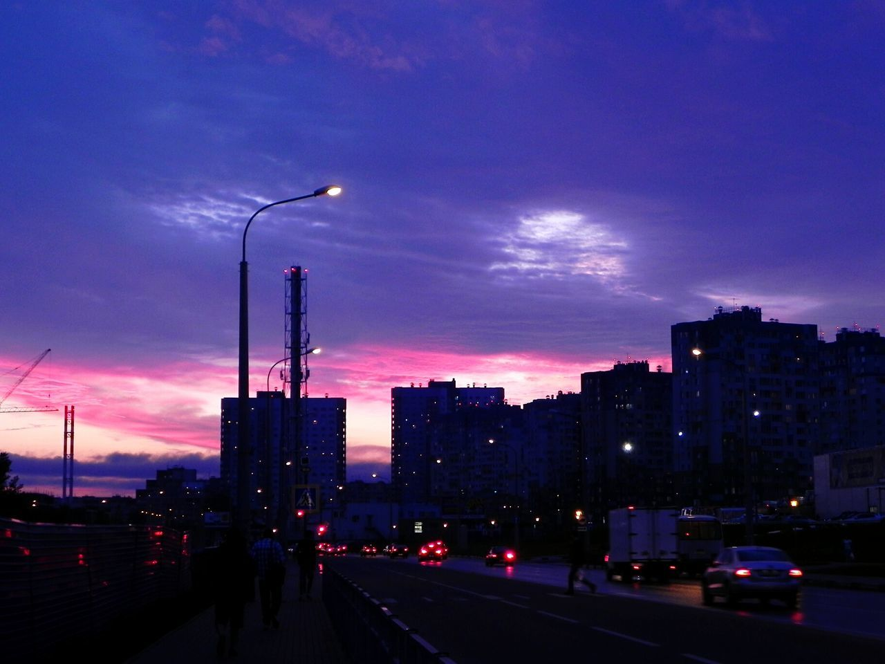 illuminated, architecture, city, sky, built structure, building exterior, road, street, transportation, car, street light, sunset, night, skyscraper, outdoors, modern, cityscape, no people
