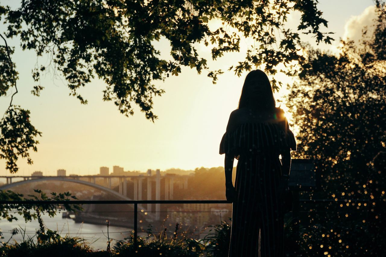 tree, rear view, silhouette, built structure, sky, architecture, city, outdoors, real people, one person, building exterior, nature, growth, women, water, day, people