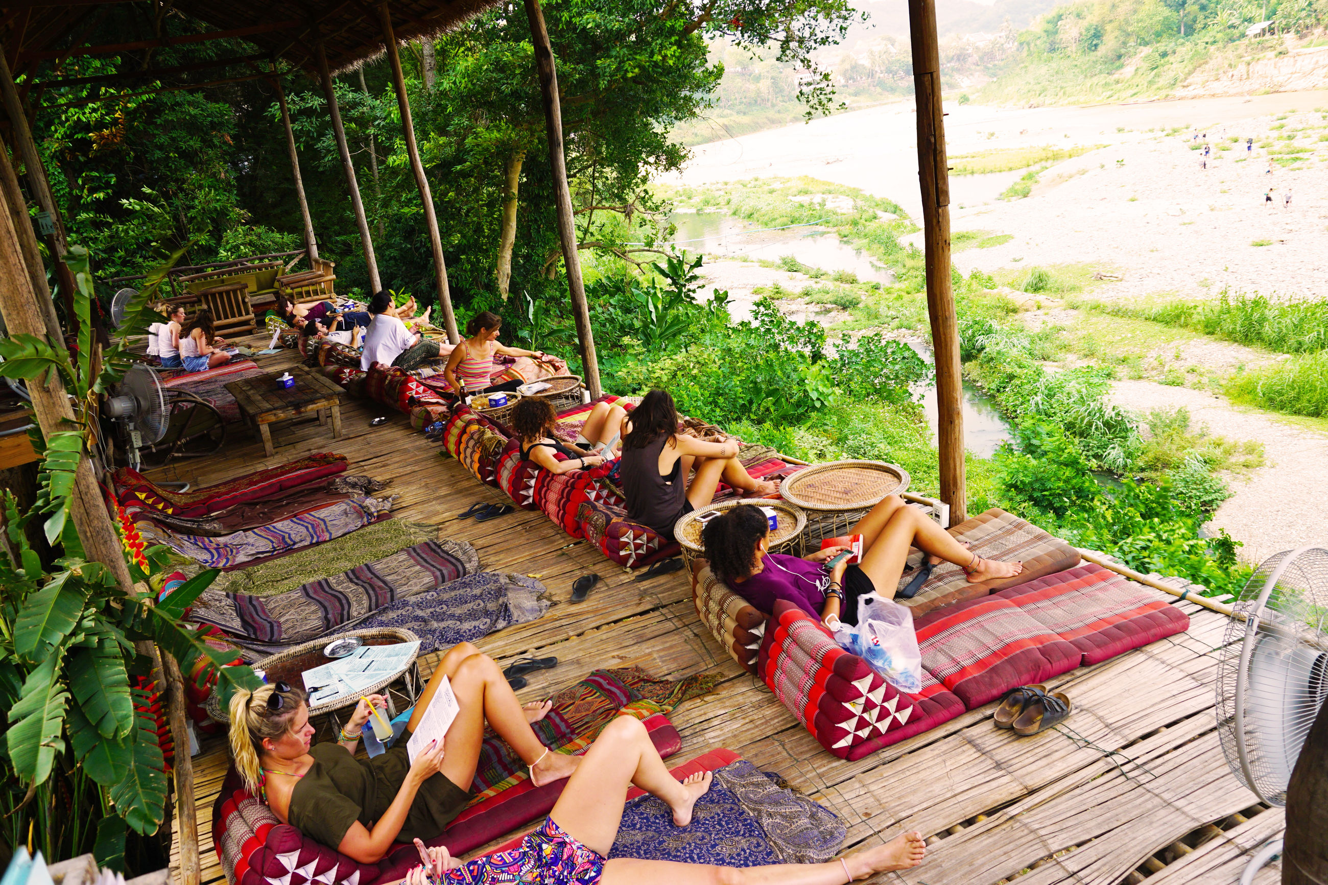 high angle view, sitting, real people, day, leisure activity, togetherness, large group of people, lying down, friendship, outdoors, weekend activities, full length, enjoyment, men, tree, vacations, lifestyles, nature, young adult, women, young women, people, adult, adults only