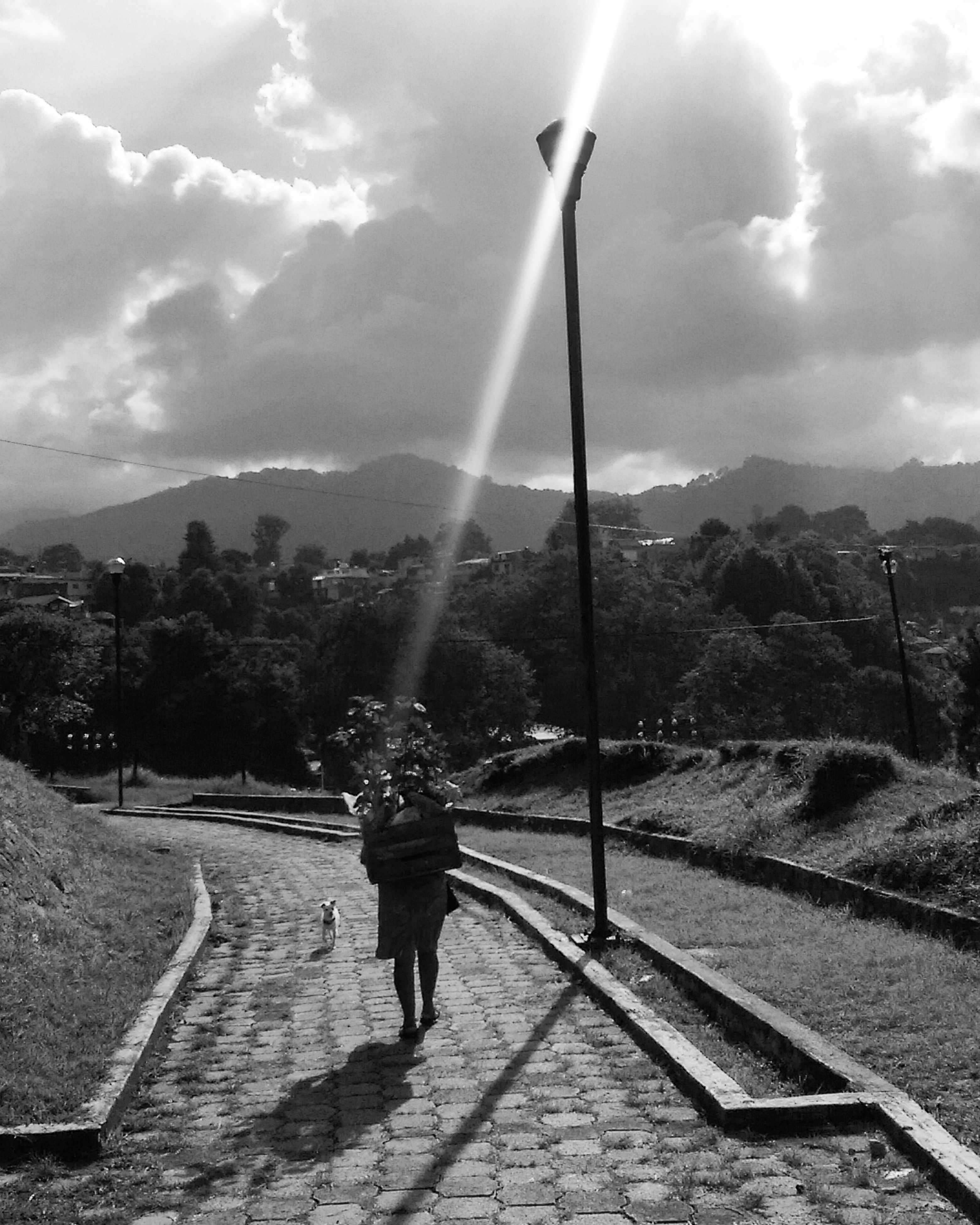 sky, lifestyles, full length, leisure activity, cloud - sky, casual clothing, sunlight, cloud, sun, sunbeam, lens flare, sunny, outdoors, day, the way forward, mountain, cloudy, nature, tourism