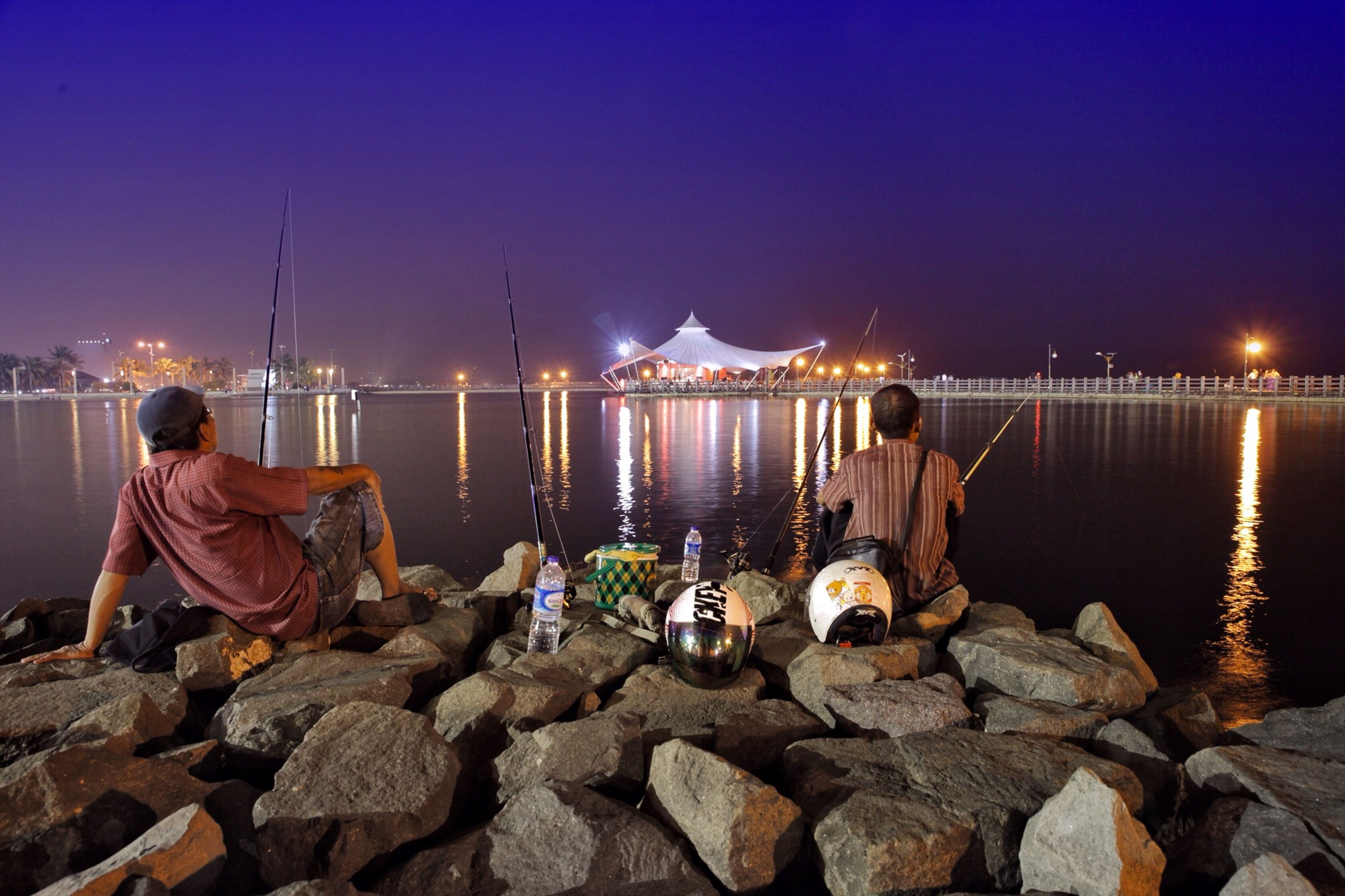 water, lifestyles, men, rear view, leisure activity, illuminated, sitting, standing, person, night, pier, casual clothing, river, togetherness, sea, sky, built structure