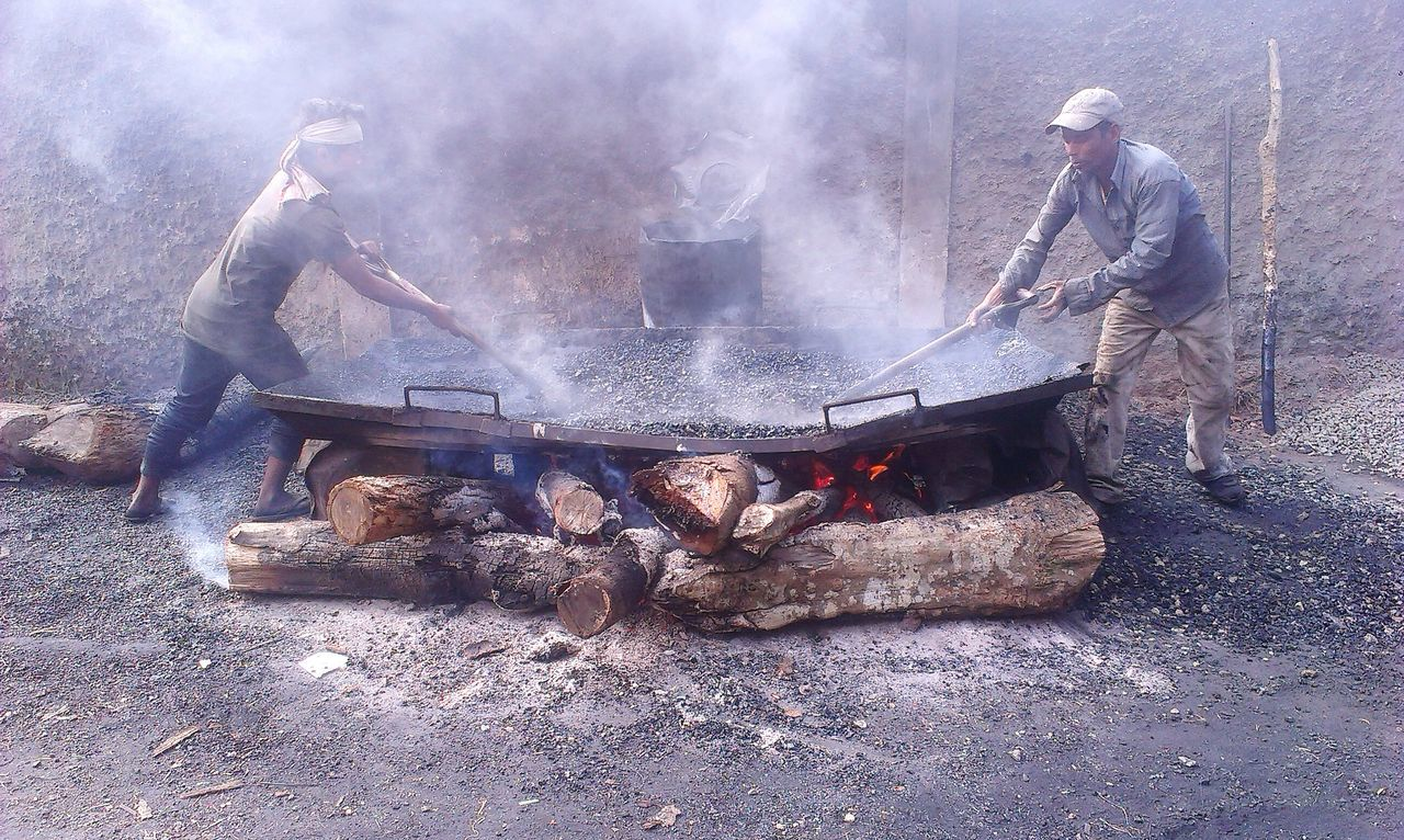 burning, smoke - physical structure, heat - temperature, flame, men, real people, full length, adult, outdoors, two people, working, only men, day, teamwork, bonfire, protective workwear, adults only, headwear, people