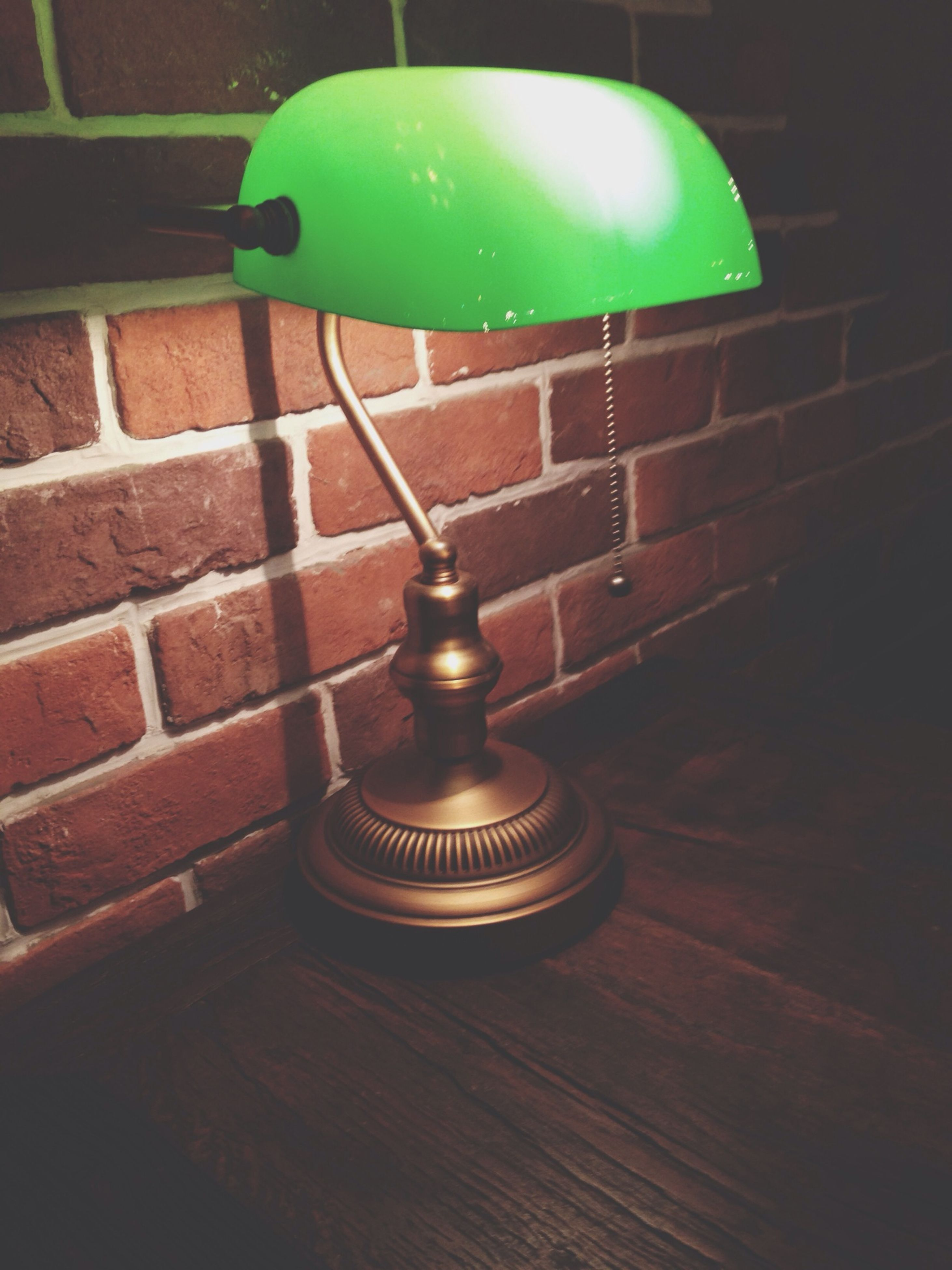 indoors, illuminated, close-up, lighting equipment, wood - material, table, no people, night, wall - building feature, still life, metal, high angle view, circle, red, pattern, green color, communication, single object, text, wooden