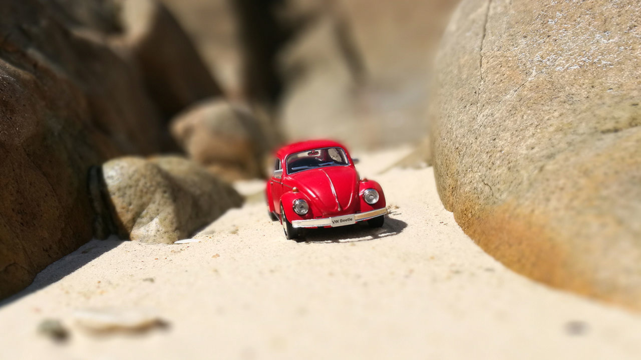 sand, selective focus, beach, rock - object, sunlight, day, outdoors, red, no people, toy car, close-up, nature, animal themes