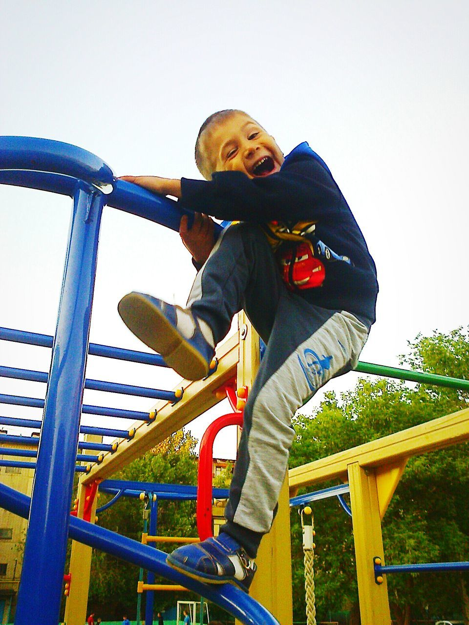 childhood, playground, elementary age, leisure activity, full length, playing, jungle gym, casual clothing, real people, slide, fun, boys, happiness, low angle view, outdoor play equipment, one person, smiling, lifestyles, park - man made space, enjoyment, front view, day, clear sky, outdoors, girls, portrait, sky, people