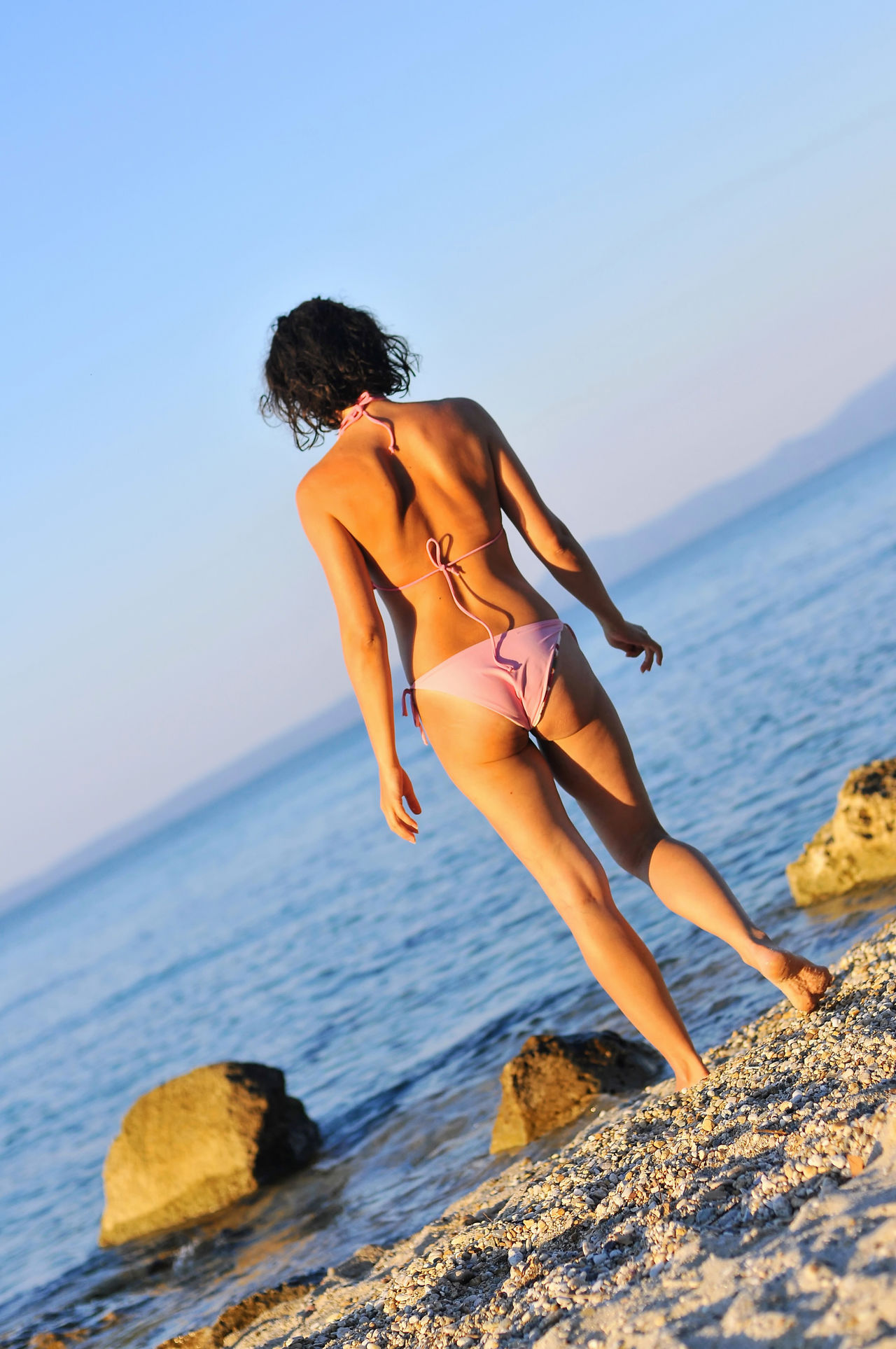 A good looking woman steeping up to the sea. Back View Of Girl Beautiful Woman Beauty In Nature Clear Sky Female Silhouette Good Looking Leisure Activity Lifestyles Nice Body Perfect Body Rock - Object Scenics Standing Stepping Up Sun Bath Sun Bathing Vacations Woman Back Woman Backside Young Adult Young Women