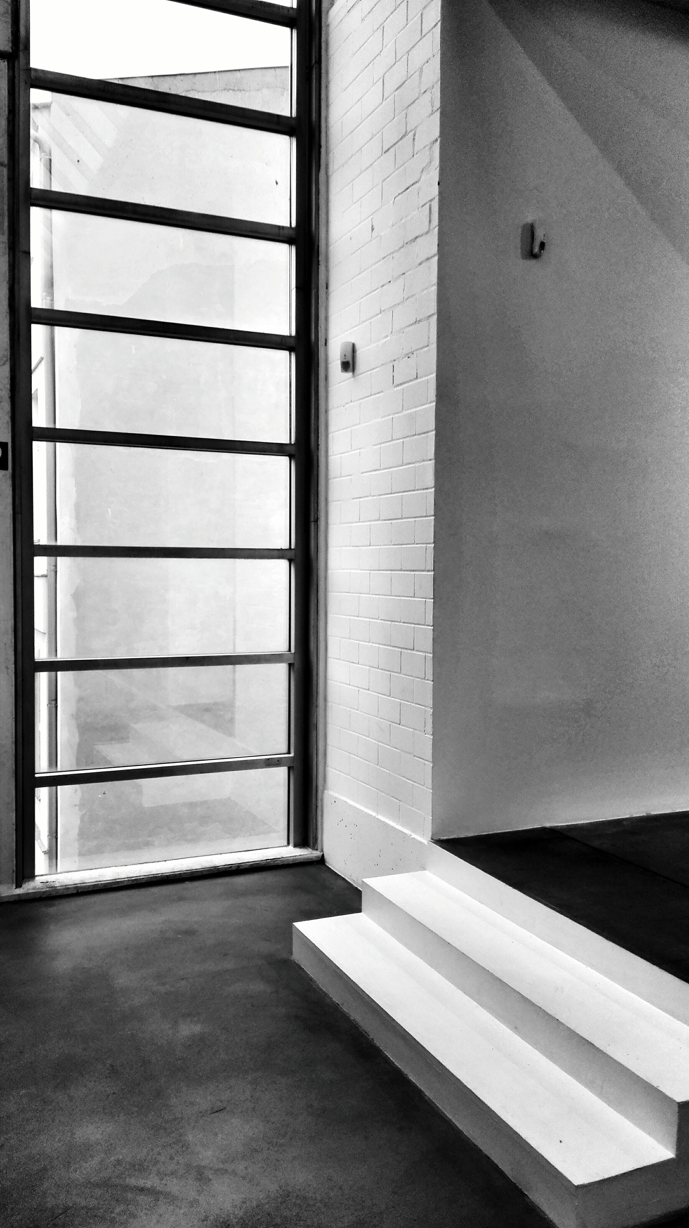 architecture, built structure, building exterior, window, indoors, wall - building feature, door, wall, shadow, building, sunlight, day, tiled floor, empty, closed, absence, no people, white color, city, entrance