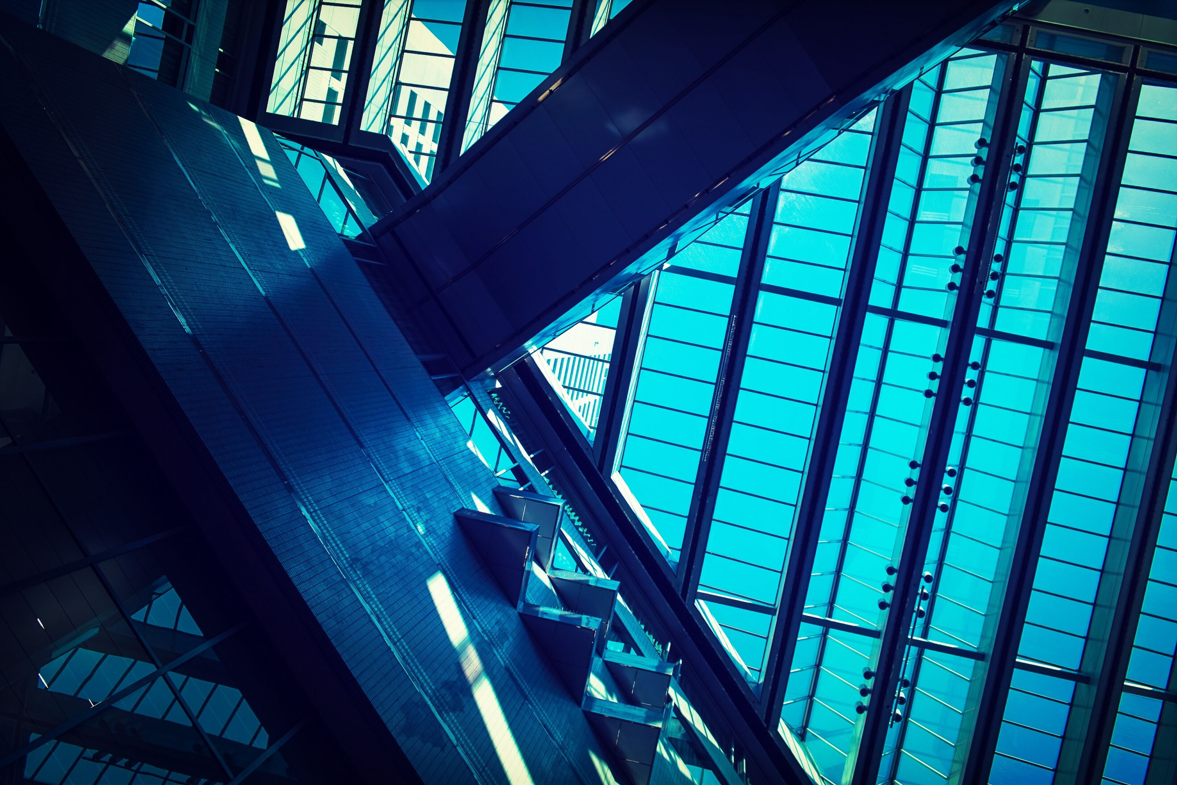 architecture, built structure, low angle view, glass - material, blue, building exterior, indoors, modern, window, transparent, sunlight, pattern, sky, building, day, no people, city, metal, reflection, architectural feature