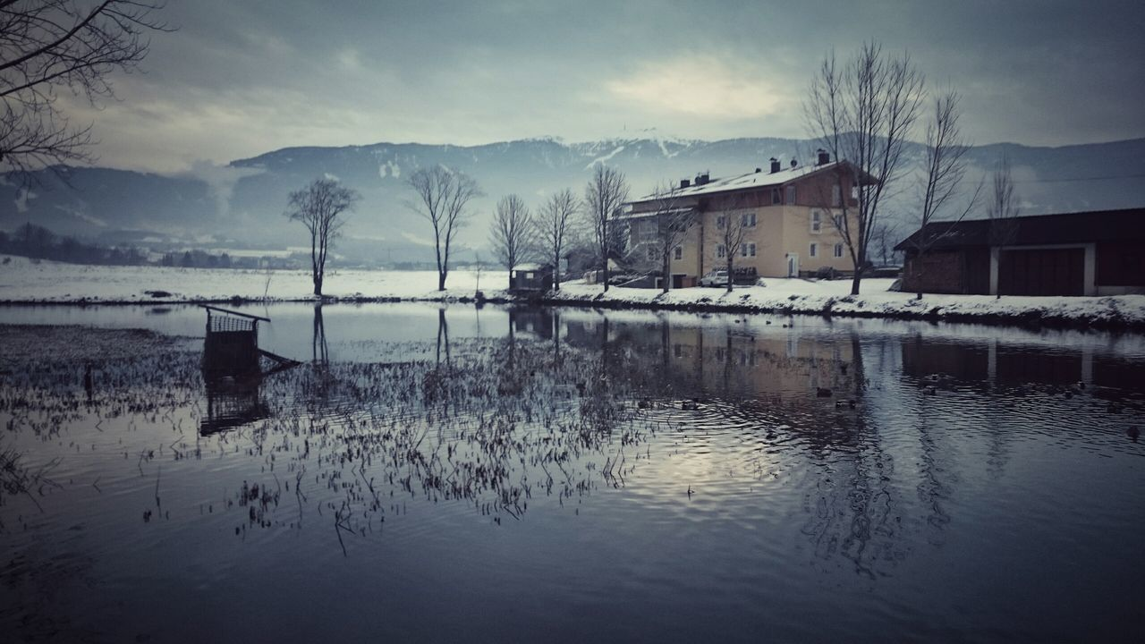 Houses At Lakeshore At Winter Against Cloudy Sky