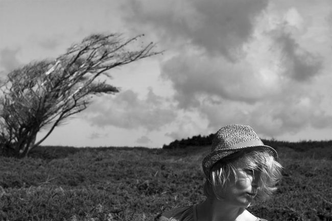 woman on a windy day Blackandwhite Blooming Casual Clothing Cloud - Sky Clouds And Sky Fashion Field Hanging Out Headshot Human Hair Melancholy Person Rebel Scenics The Daylight  Vacations Wind Window Woman Working Young Adult