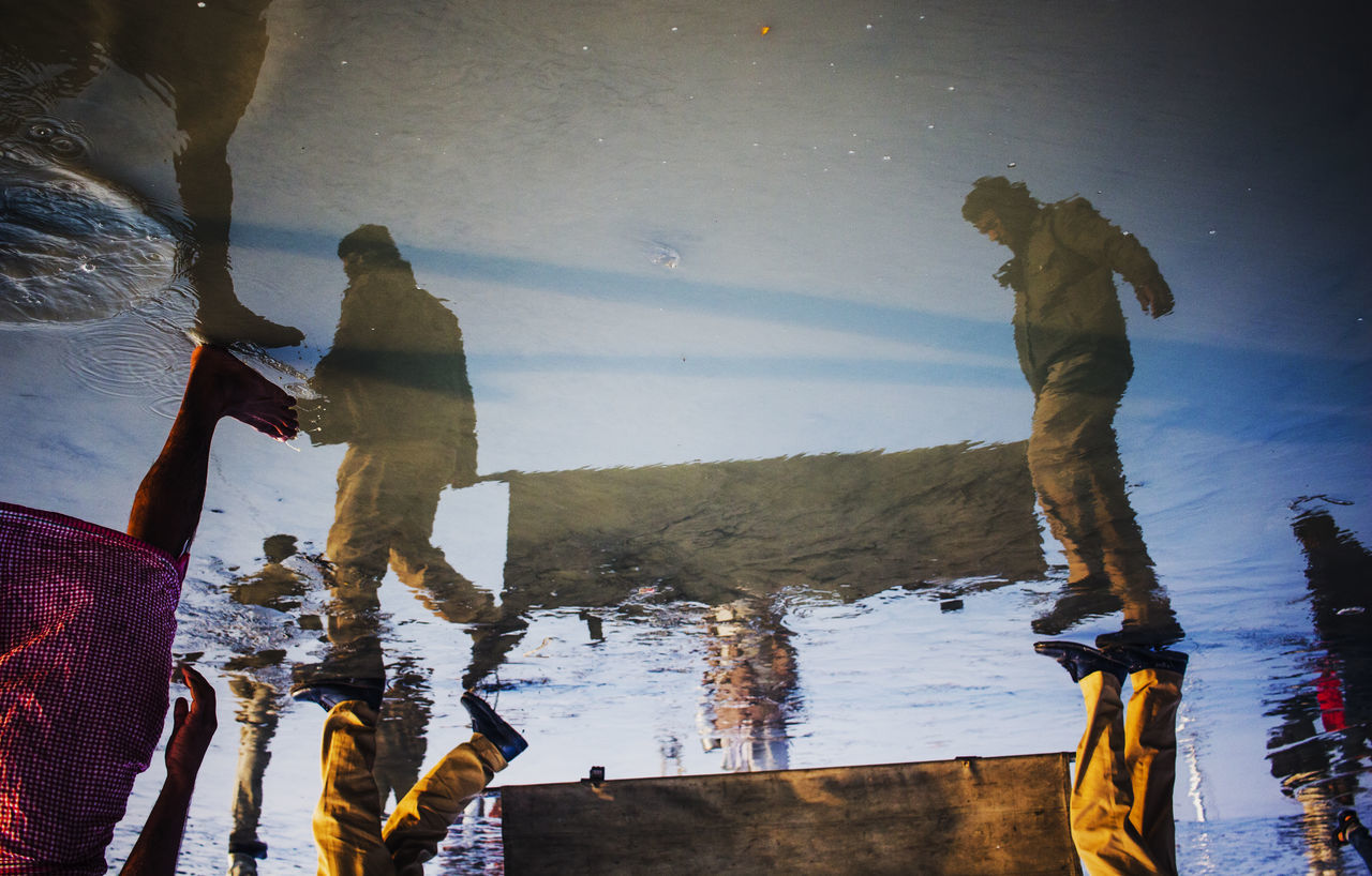 Two Policemen were going to rescue a Patient at the riverbank. The Reflection of them on the water was taken. colour of life Daily lifestyles people Photojournalism Reflection Reflection street photography streetphotography two people water Winter