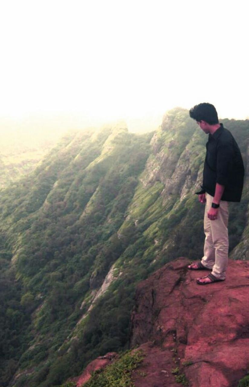 one person, full length, standing, casual clothing, mountain, landscape, tranquil scene, tree, leisure activity, nature, real people, hiking, side view, scenics, day, adventure, men, lifestyles, outdoors, beauty in nature, young adult, one man only, clear sky, sky, adult, only men, people, adults only