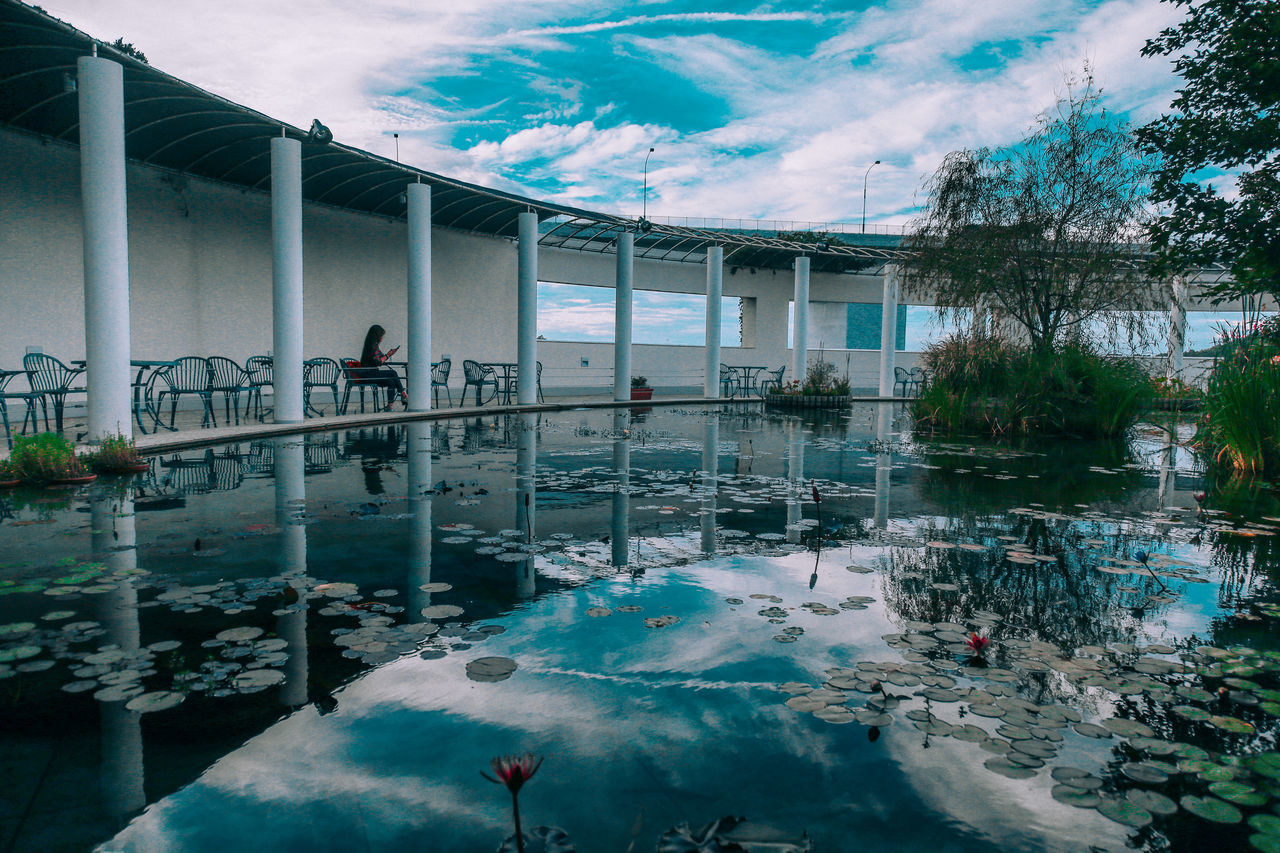 // chilling by the pond // Architecture Beauty In Nature Blue Building Exterior Built Structure Cloud - Sky Day Full Length Men Mirror Nature One Person Outdoors Real People Reflection Reflection Reflection_collection Reflections Shootermag Shootermagazine Sky The Great Outdoors - 2017 EyeEm Awards Tree Water Women