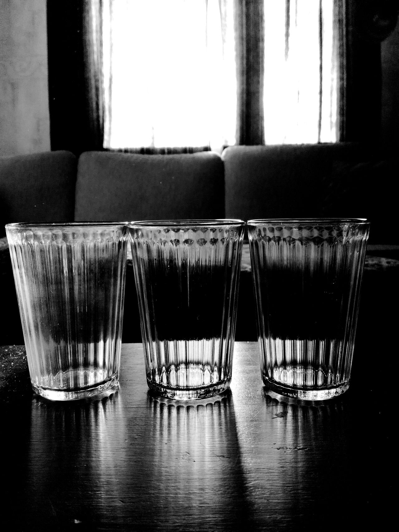 Indoors  No People Table Day Glasses Transparency Light And Shadow Dark And Light In Front Sun Through The Window Foreground Focus Blackandwhite Drinking Glasses Used After Party Sofa Curtains Used Glass Day After  Trio