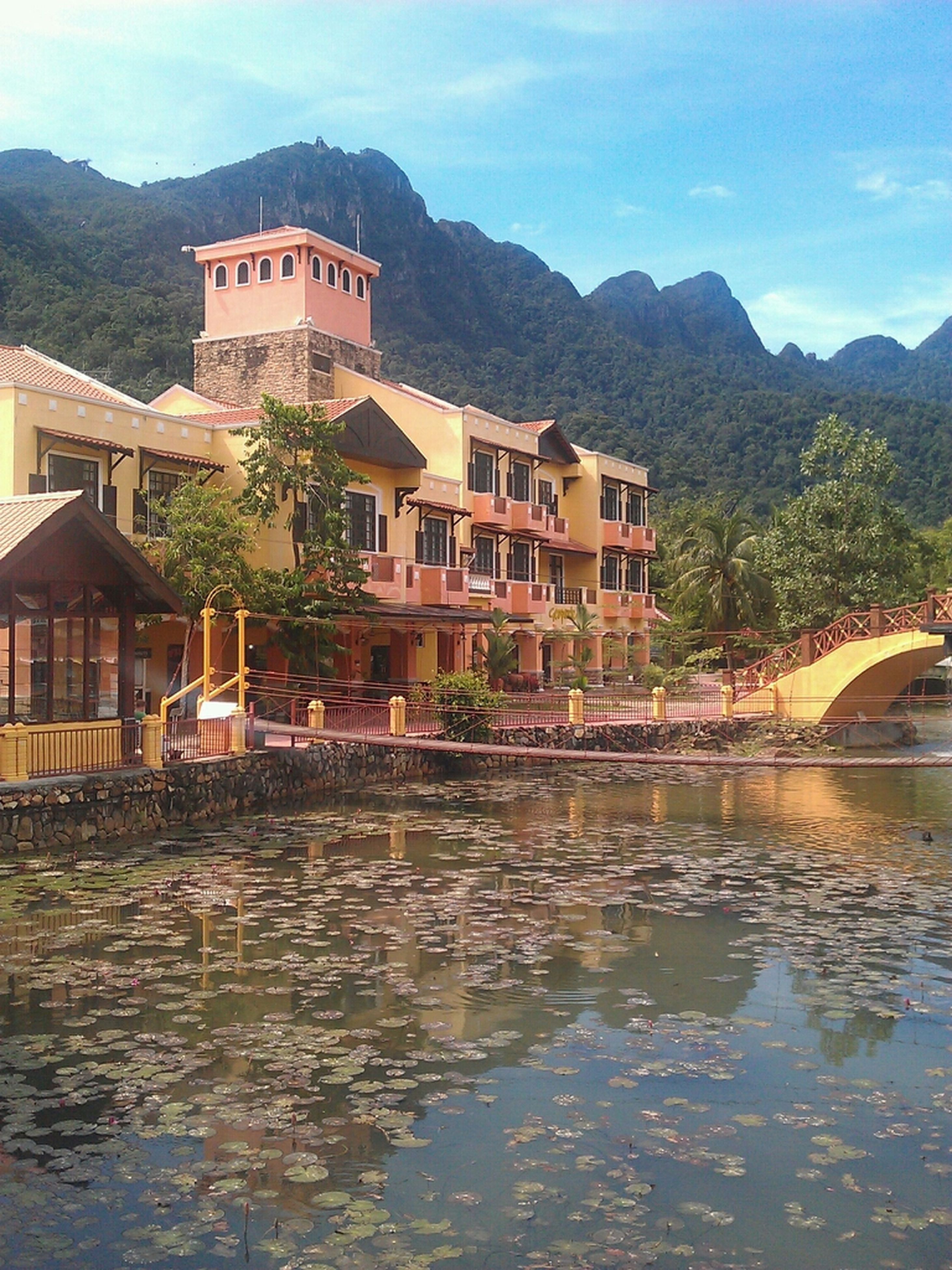 architecture, built structure, building exterior, water, mountain, waterfront, house, reflection, river, sky, mountain range, lake, residential structure, residential building, town, canal, outdoors, nature, tree, day