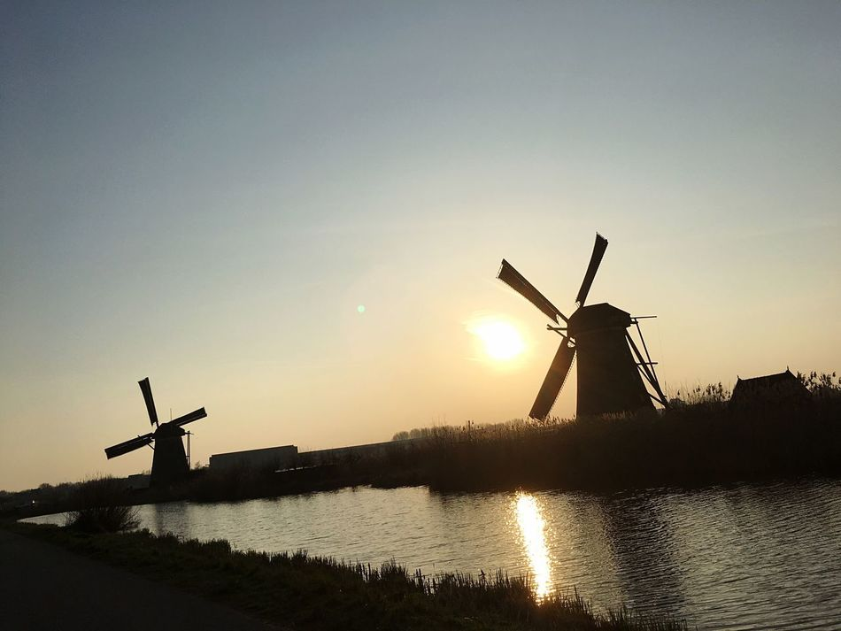 Fuel And Power Generation Wind Power Environmental Conservation Windmill Wind Turbine Alternative Energy Renewable Energy Traditional Windmill Rural Scene Built Structure Water Sunset Nature No People Silhouette Outdoors Sky Architecture Technology Watermill