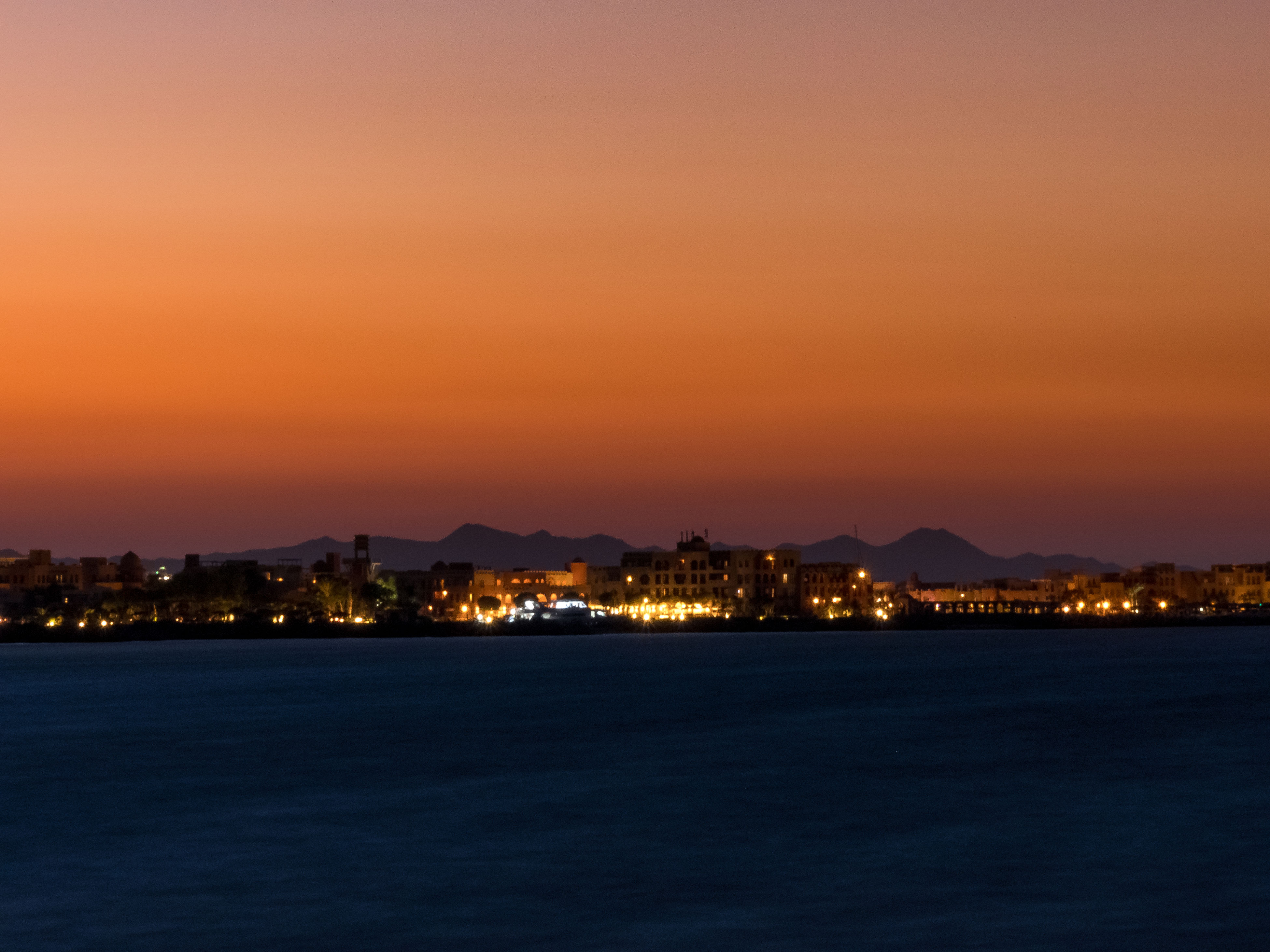 sunset, illuminated, city, night, cityscape, reflection, dusk, sky, mountain, no people, architecture, water, scenics, sea, outdoors, beauty in nature, urban skyline, nature