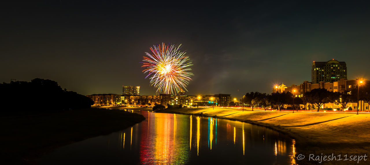 night, illuminated, firework display, firework - man made object, celebration, building exterior, exploding, long exposure, sky, waterfront, river, outdoors, reflection, built structure, architecture, arts culture and entertainment, event, cityscape, city, no people, water, travel destinations, clear sky