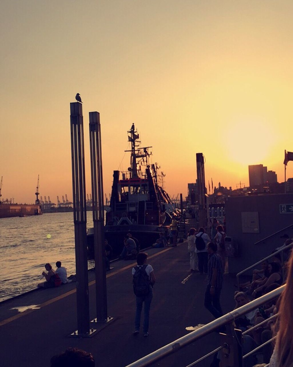 sunset, built structure, sea, clear sky, sky, large group of people, silhouette, men, architecture, lifestyles, real people, nautical vessel, building exterior, city, outdoors, cityscape, people, adult, day