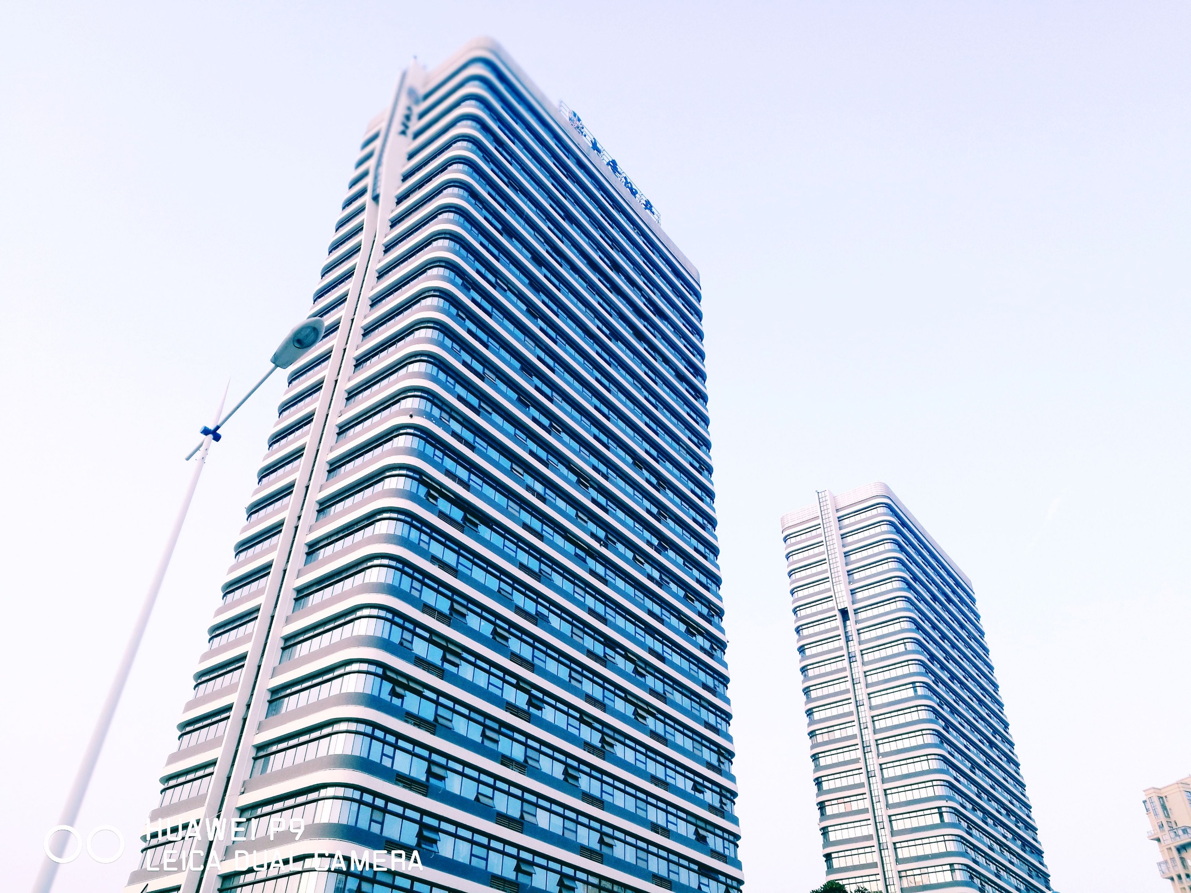 low angle view, architecture, building exterior, skyscraper, built structure, city, modern, clear sky, outdoors, no people, day, sky, connection, technology