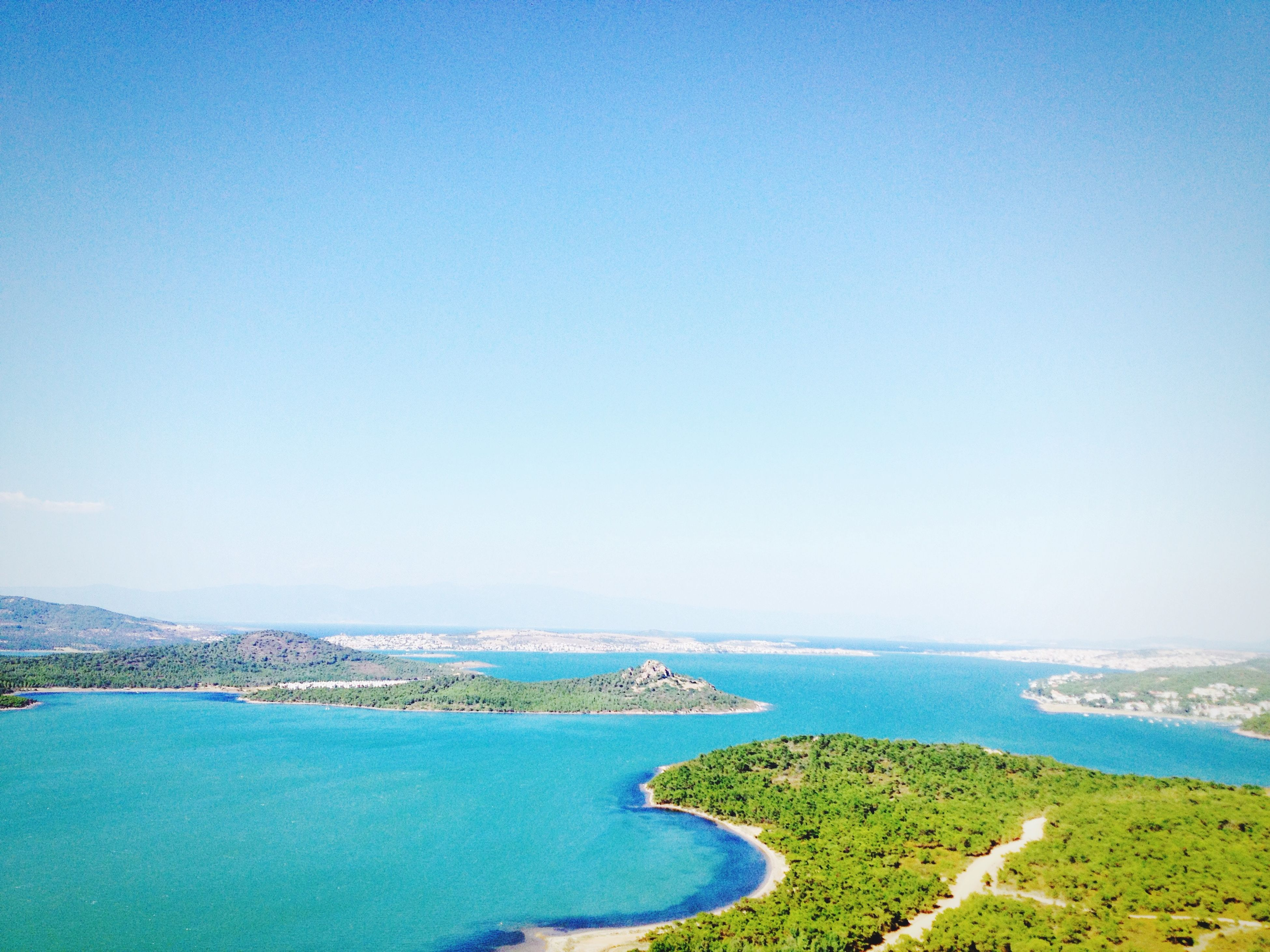 blue, water, sea, clear sky, copy space, tranquil scene, scenics, tranquility, beauty in nature, nature, horizon over water, coastline, high angle view, idyllic, day, beach, outdoors, shore, ocean, landscape