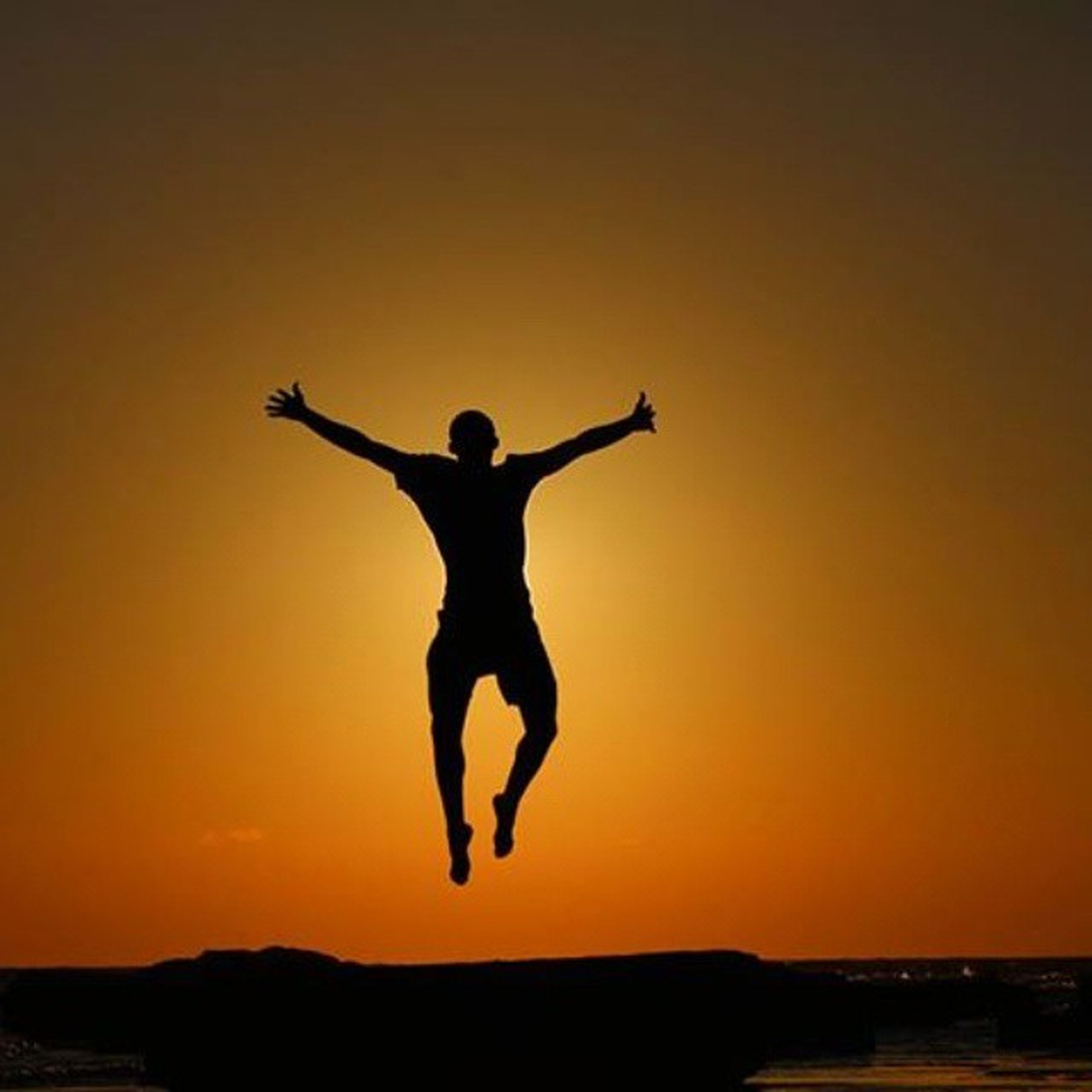 sunset, full length, silhouette, arms outstretched, leisure activity, lifestyles, orange color, mid-air, standing, jumping, arms raised, clear sky, copy space, freedom, sky, carefree, tranquil scene, nature