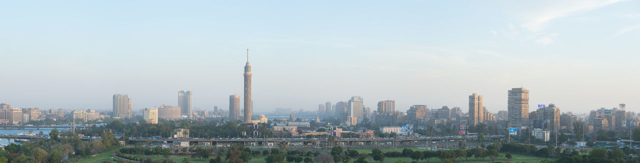 Wide panoramic view of central Cairo skyline at dusk, the Nile river, the Island of Zamalek and the 6th October Bridge. Africa Architecture Building Exterior Cairo Cairo Egypt City City Life Cityscape Day Egypt Landmark Middle East Modern Near East Outdoors Panorama Panoramic Sky Skyscraper Travel Destinations Urban Skyline Zamalek
