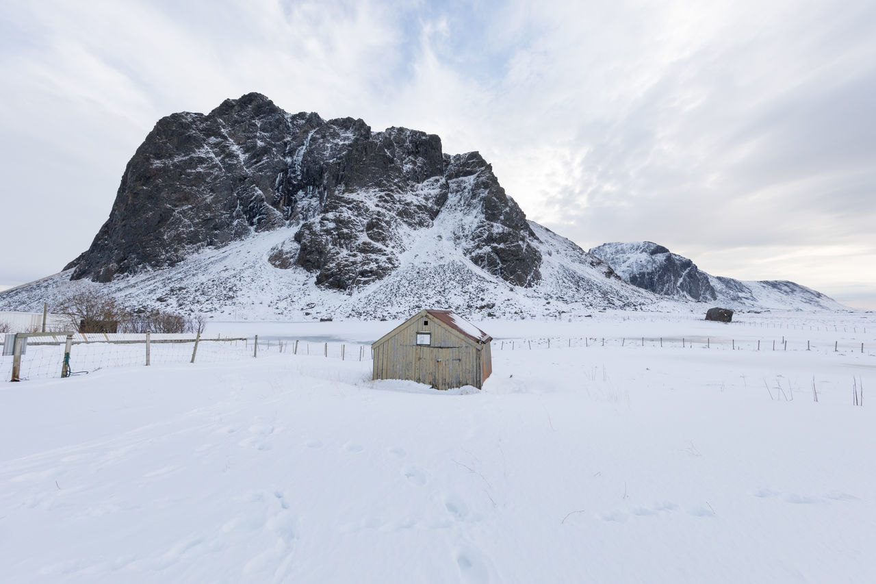 Wide angle shot of a whole mountain with small cottage in front of it in winter Architecture Beauty In Nature Building Exterior Built Structure Cloud - Sky Cold Temperature Cottage Day Fence Frozen Lake Landscape Lofoten And Vesteral Islands Mountain Nature Outdoors Remote Scenics Shoe Print Snow Tranquility White Color Wide Angle Winter Wood - Material The Great Outdoors - 2017 EyeEm Awards