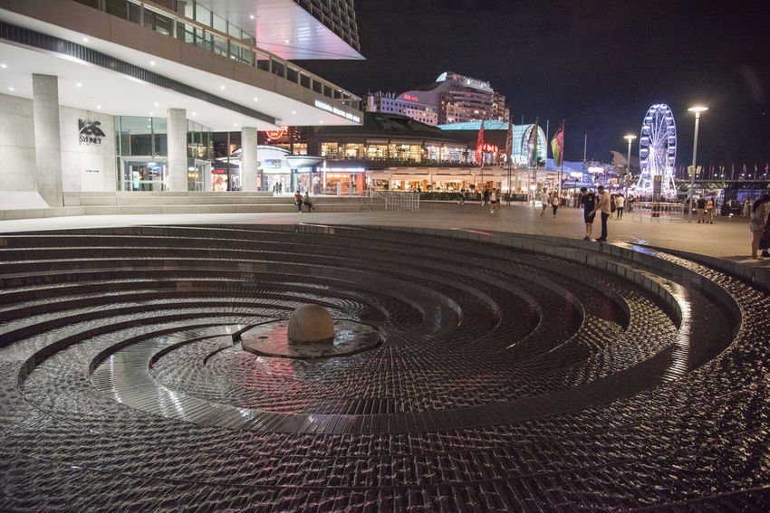 SYDNEY,NSW,AUSTRALIA-NOVEMBER 21,2016: Darling Harbour Woodward Water Fountain with people at night in Sydney, Australia. ArtWork Australia Feature Ferris Wheel Flowing Fountain Harbor Night Lights Night Life Tier Walking Around Woodward Below Ground Cascading Darling Design Harbourside Shopping Center Incidental People Night Repetition Robert Woodward Spiral Swirl Sydney Water