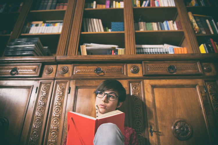 Young woman student with books and library in background Book Bookcase Brunette Education Eyeglasses  Homework Knowledge Library NotePad Notes One Person People Pretty Red Student Studying Studying Time University Woman Young