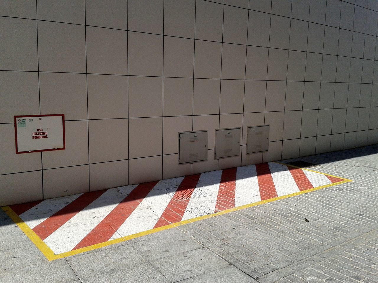 High Angle View Of Marking On Street By Building During Sunny Day